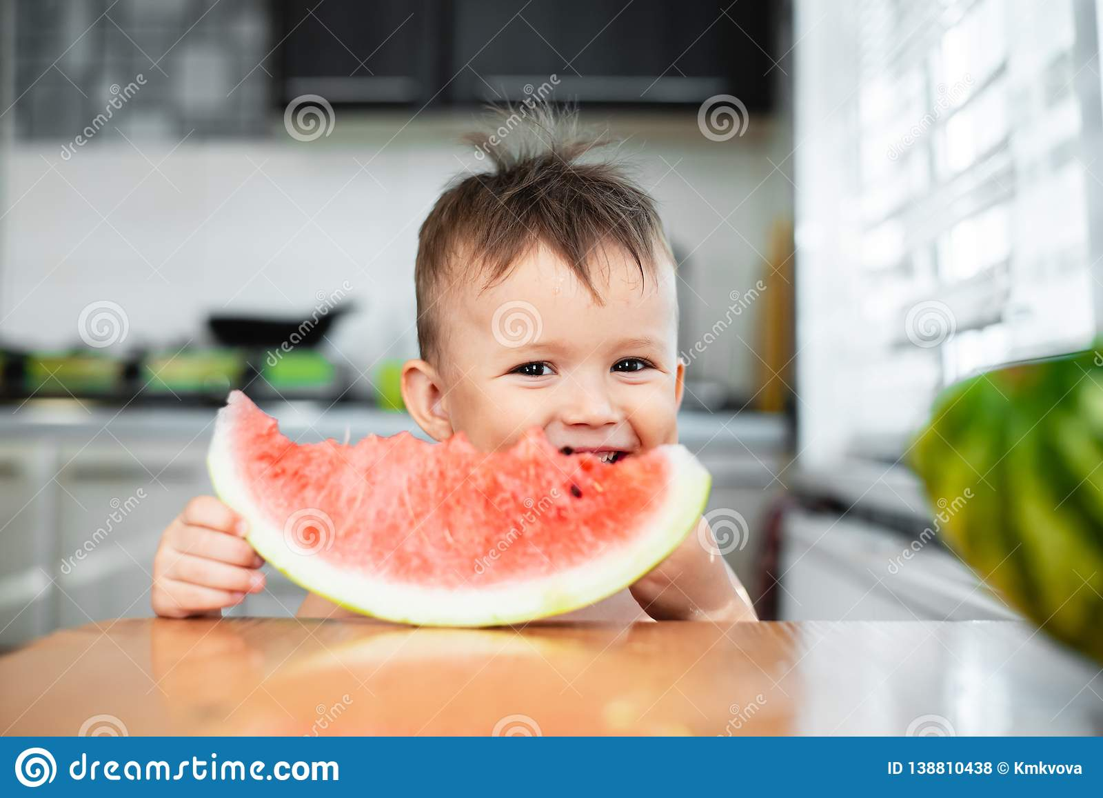 Petit garçon mignon mangeant la pastèque dans la cuisine