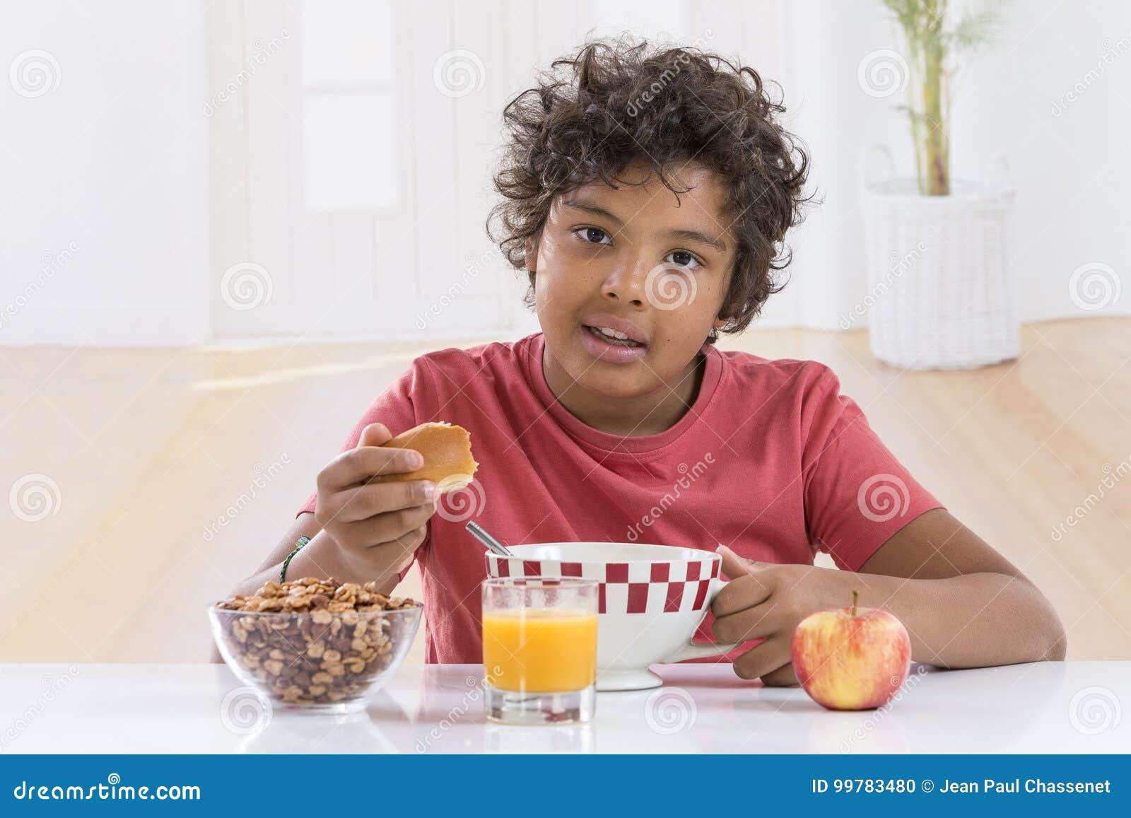 Petit garçon mignon prenant le petit déjeuner à la maison buvant un grand bol de lait dans le T-shirt de lblue