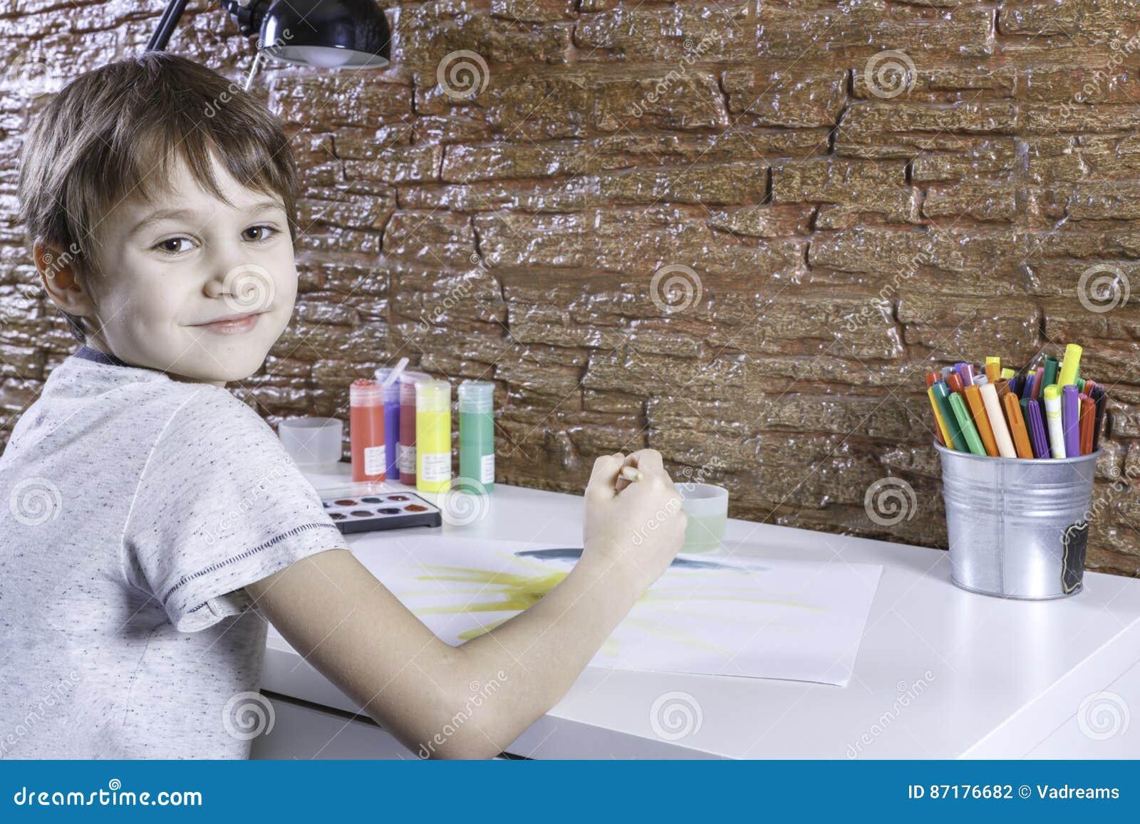 Petit garçon mignon s asseyant à la table et à la photo de peinture