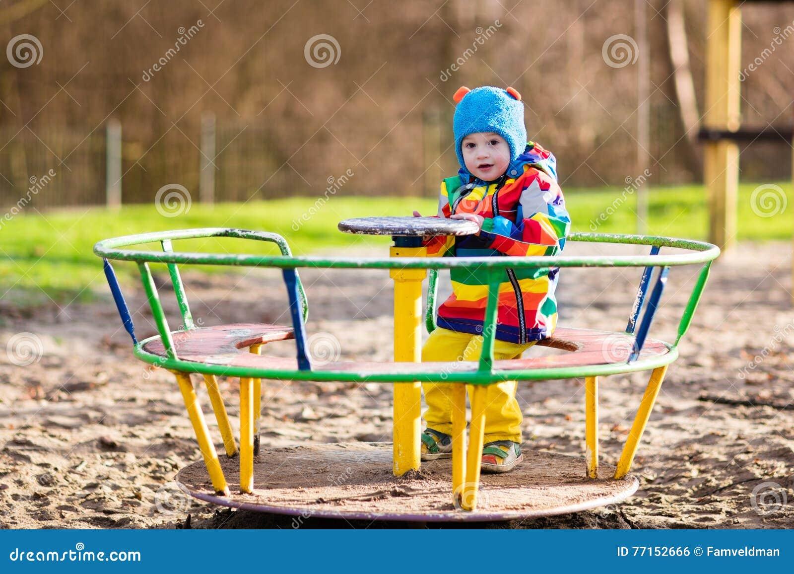 Petit garçon sur le terrain de jeu en automne