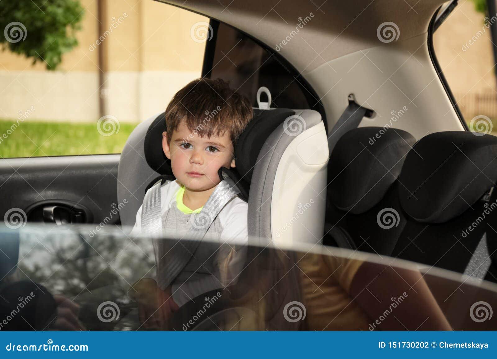 Petit garçon triste s asseyant dans seul le siège de sécurité à l intérieur de la voiture