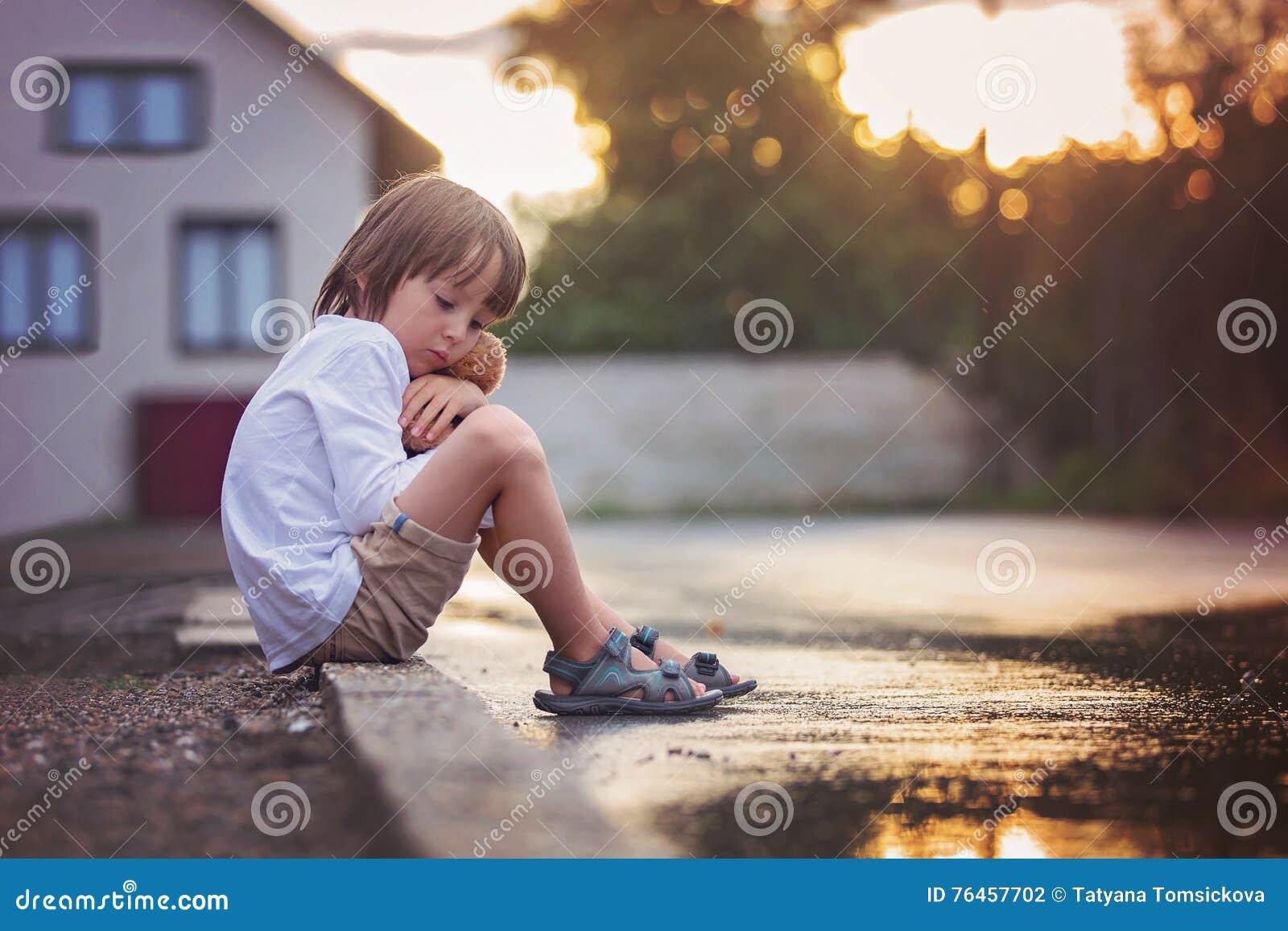 https://thumbs.dreamstime.com/z/petit-gar%C3%A7on-triste-s-asseyant-sur-la-rue-sous-la-pluie-%C3%A9treignant-son-t-76457702.jpg