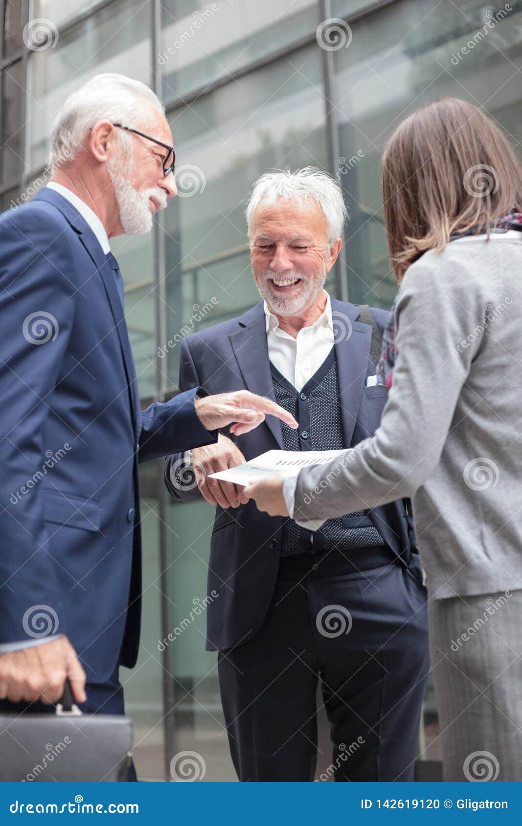 Petit groupe mixte d hommes d affaires ayant une réunion, discutant des rapports de ventes