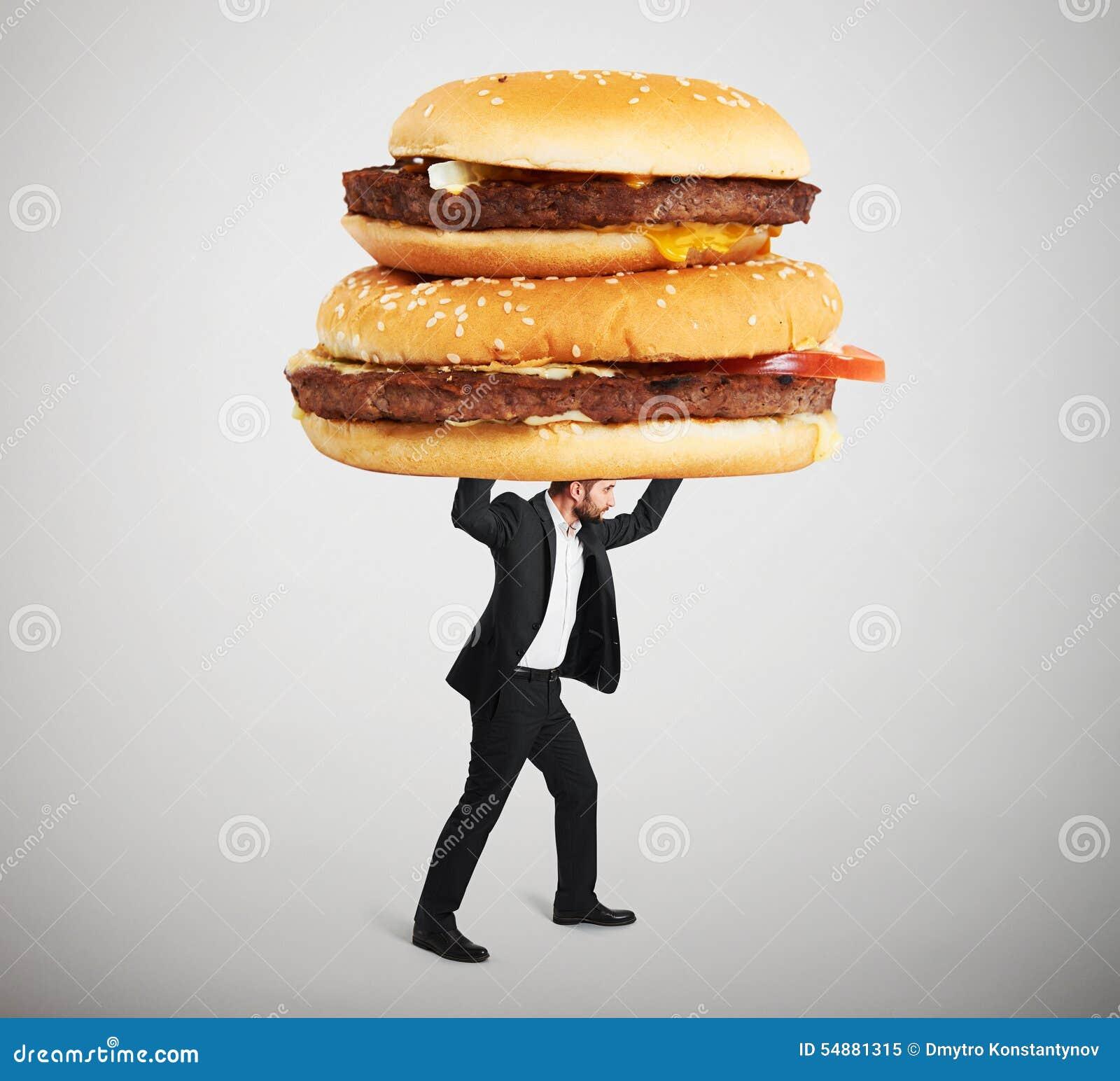 Petit homme portant de grands sandwichs