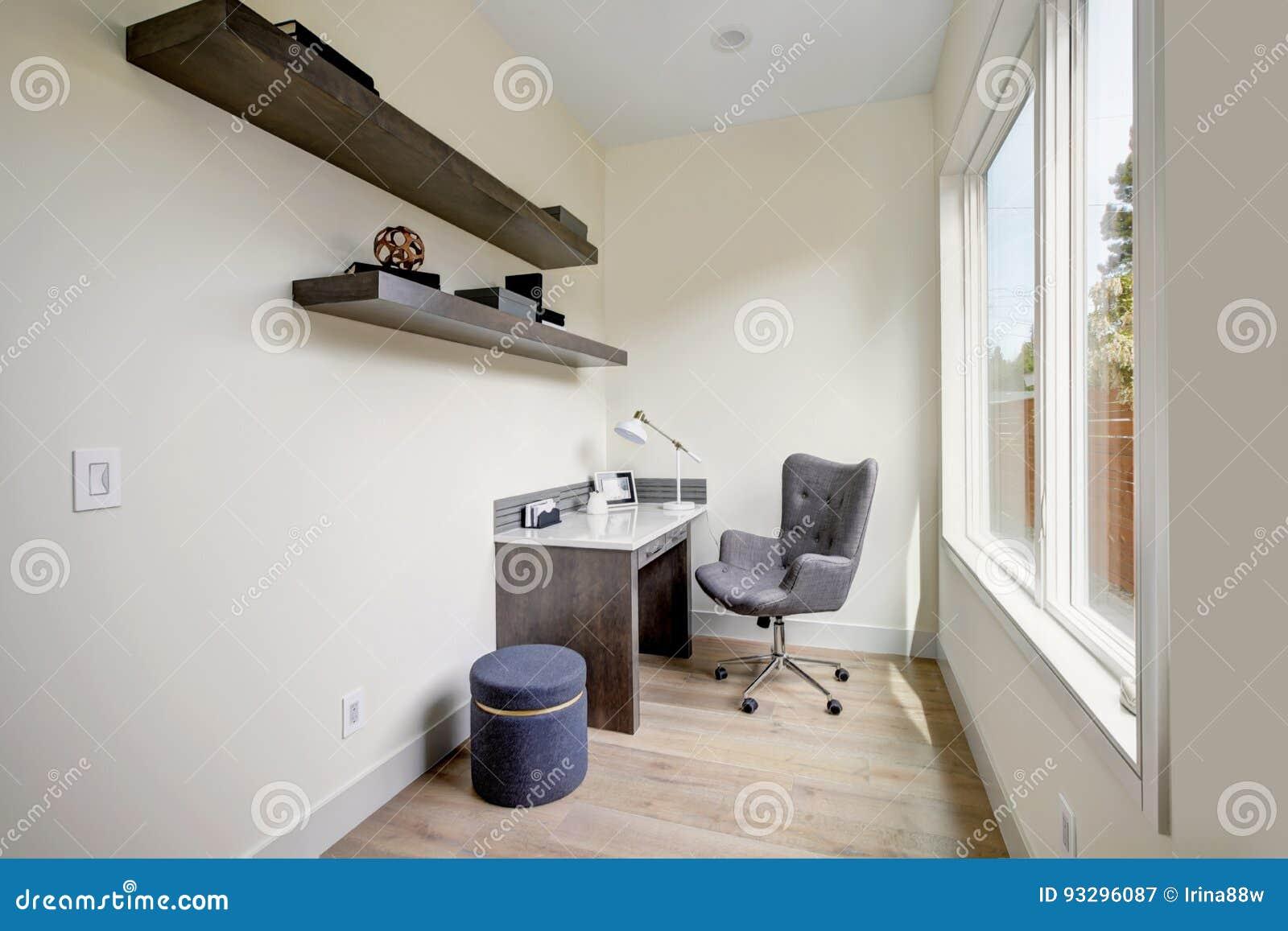 Petit intérieur léger de siège social avec le bureau faisant le coin et une chaise