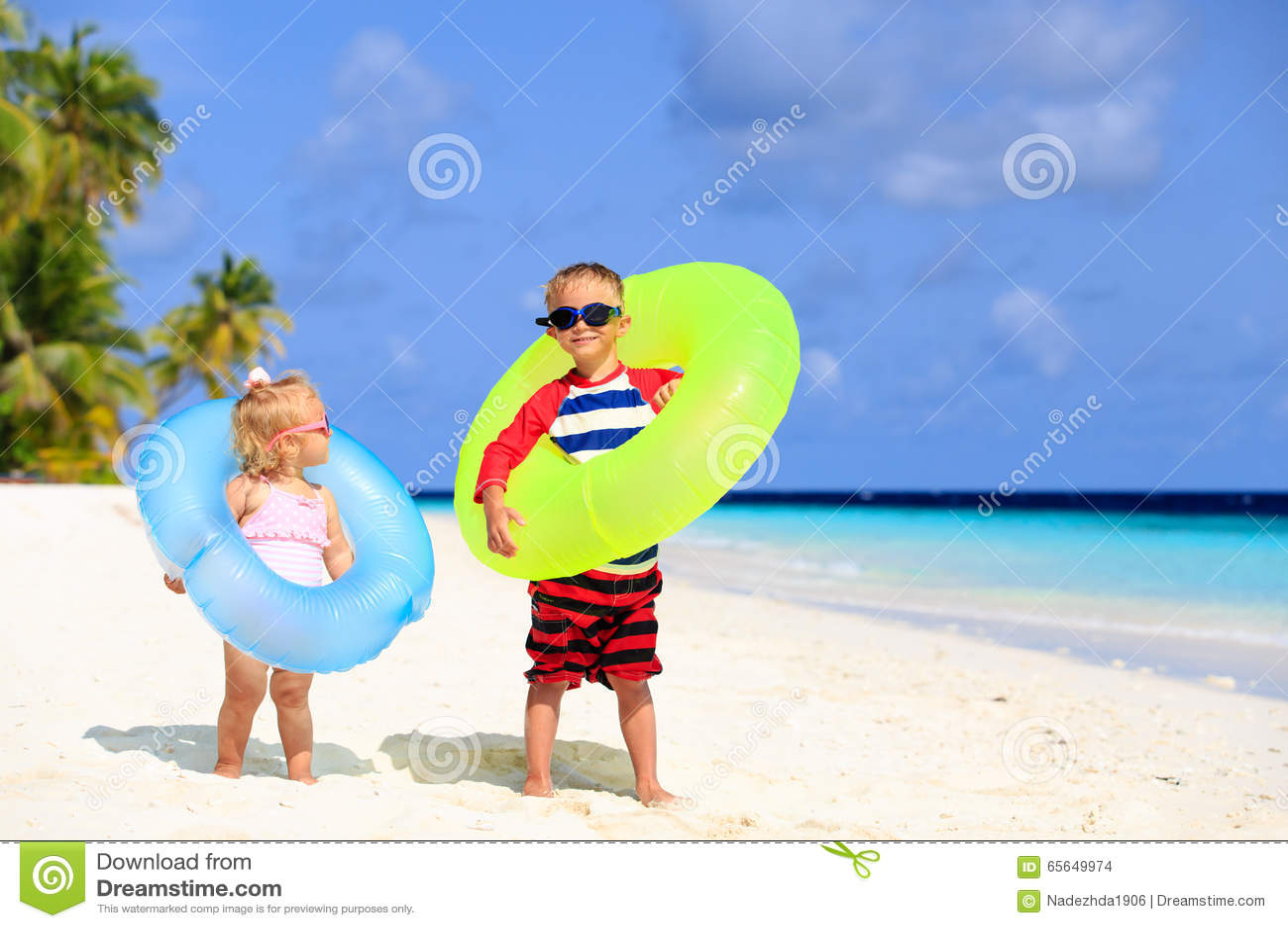 Petit la fille mignonne de garçon et d enfant en bas âge jouent sur la plage