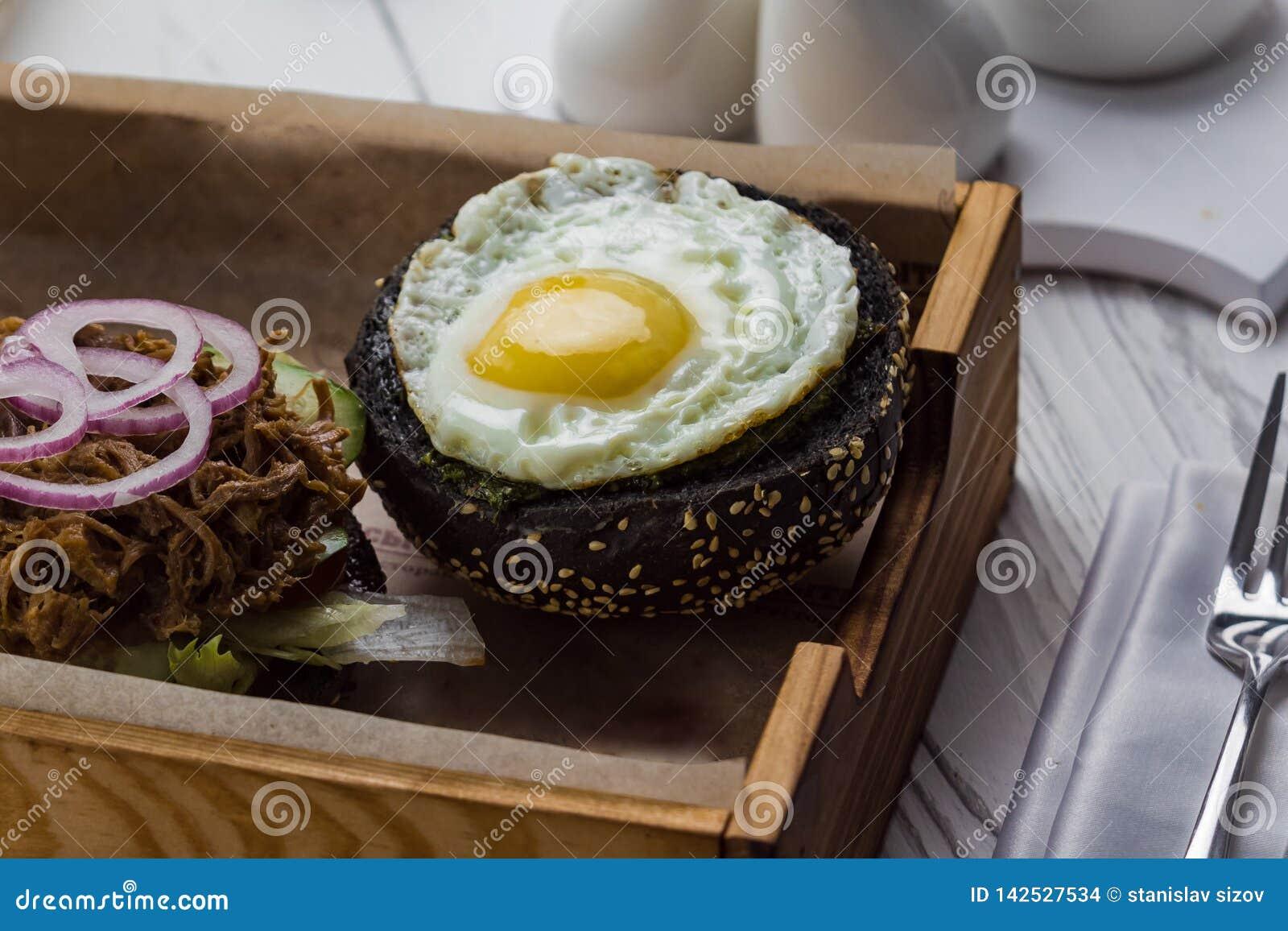 Petit pain avec l oeuf au plat, la viande et les légumes