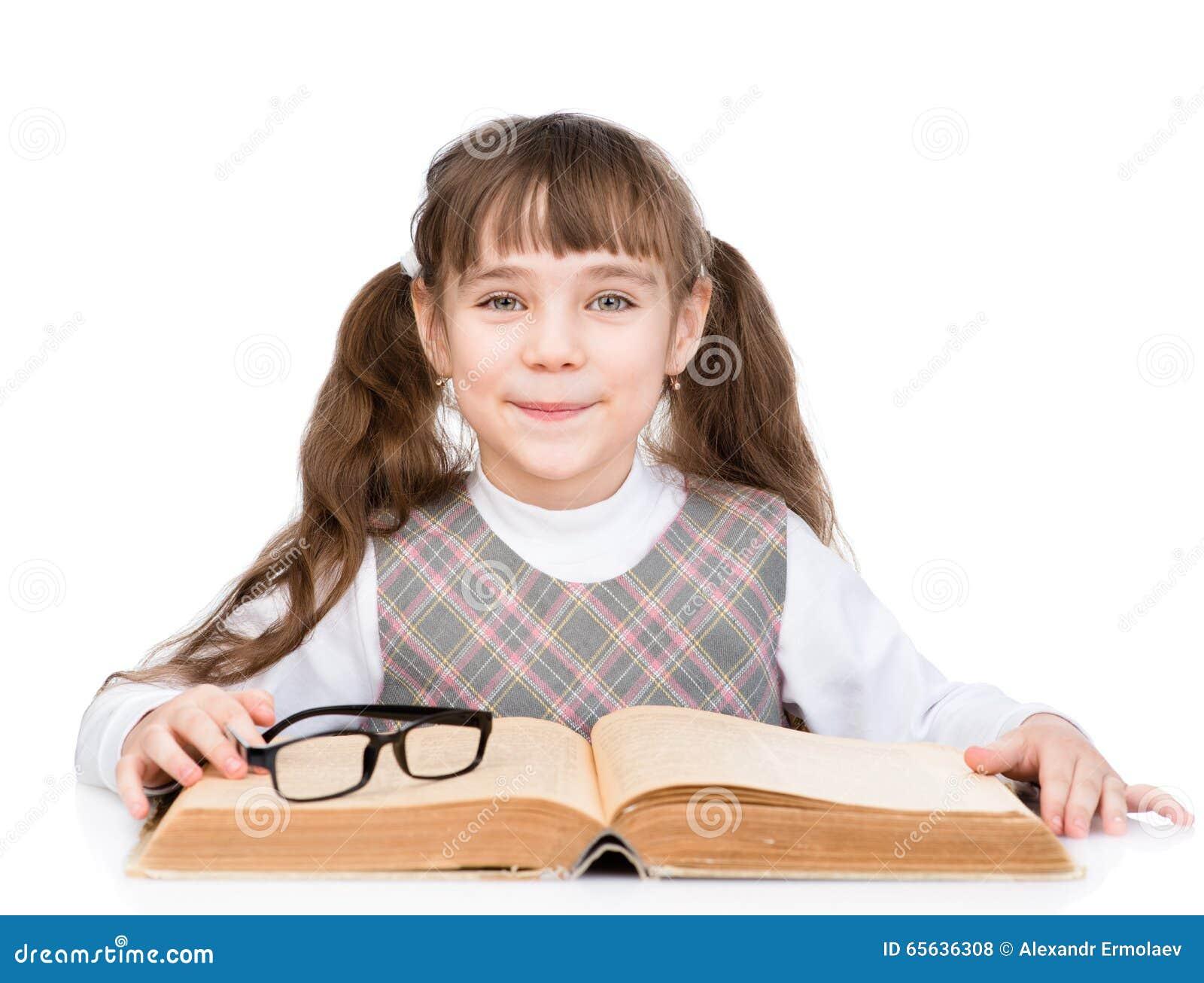 Petite écolière avec le grand livre D isolement sur le fond blanc