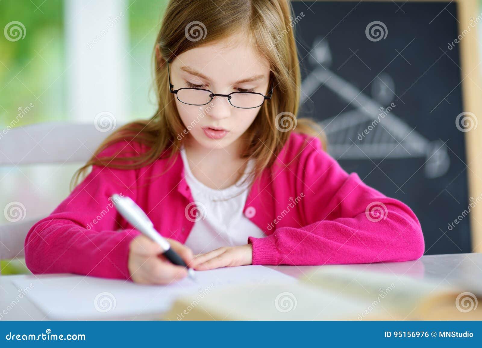 Petite écolière futée avec le stylo et livres écrivant un essai dans une salle de classe Enfant dans une école primaire