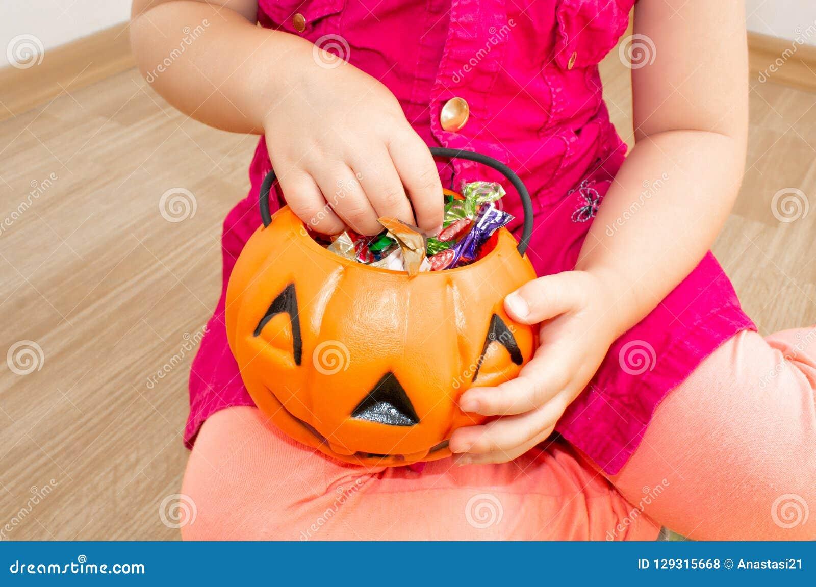 Petite belle fille s asseyant avec un potiron avec des sucreries dans des ses mains, Halloween