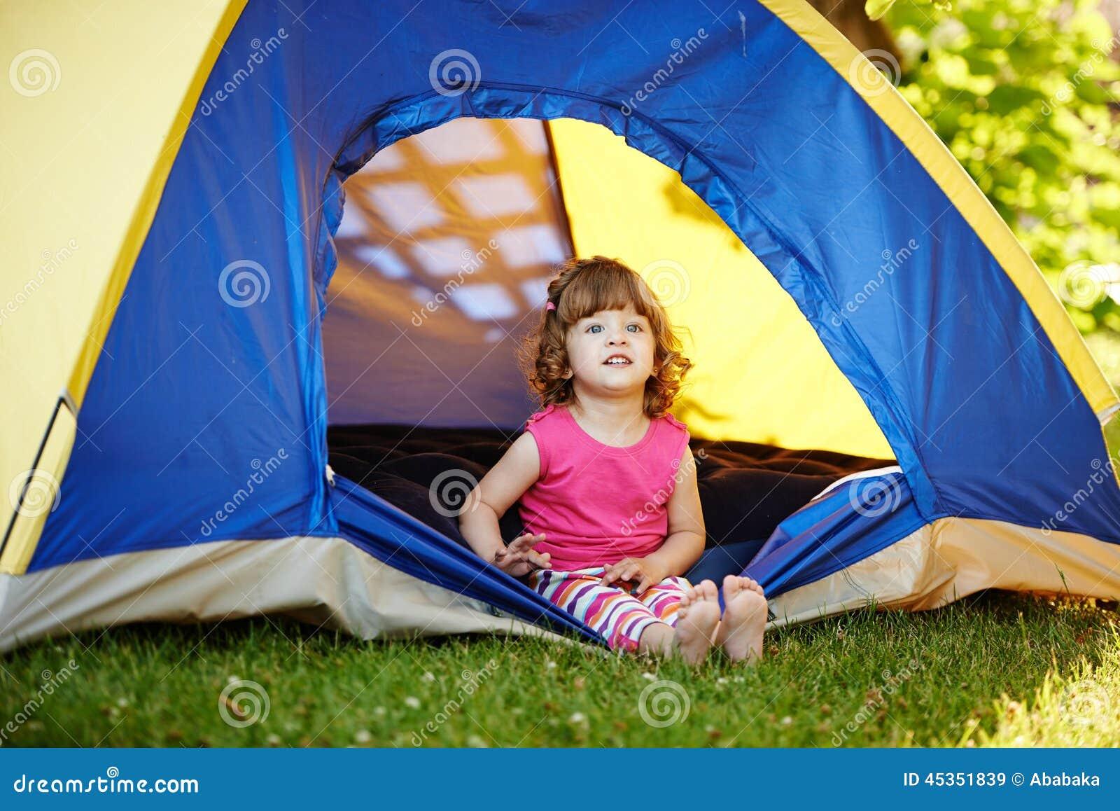 Petite belle fille s asseyant dans la tente