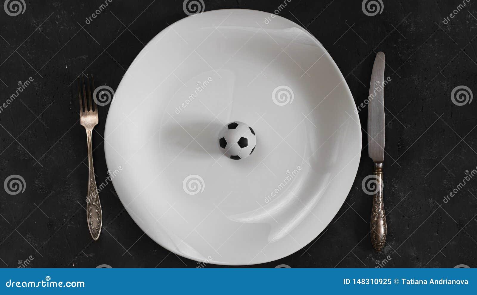Petite boule du football du plat blanc avec la fourchette et du couteau sur le fond texturis? de tableau Horizontal avec l espace