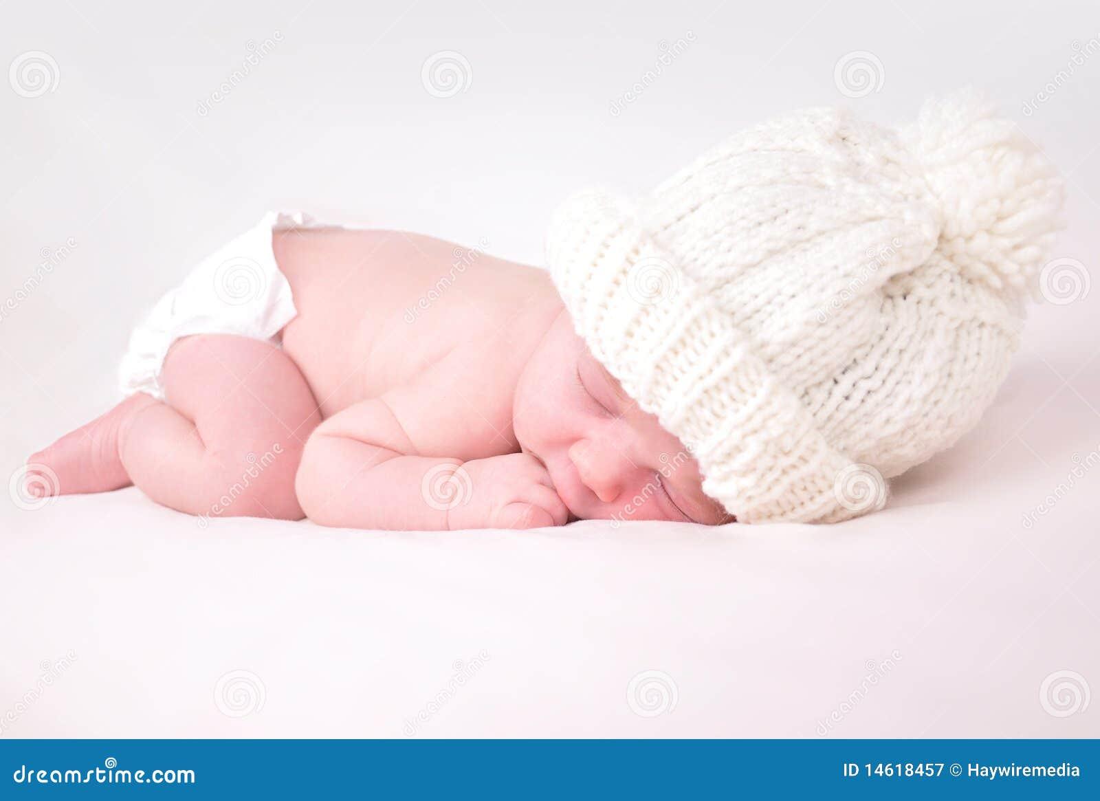 Petite chéri nouveau-née dormant sur le fond blanc