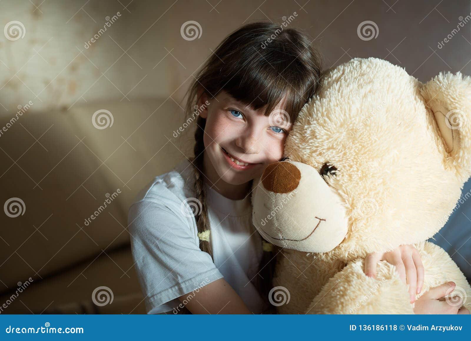 Petite fille étreignant l ours de nounours d intérieur dans sa chambre, concept de dévotion, jouet de Big Bear