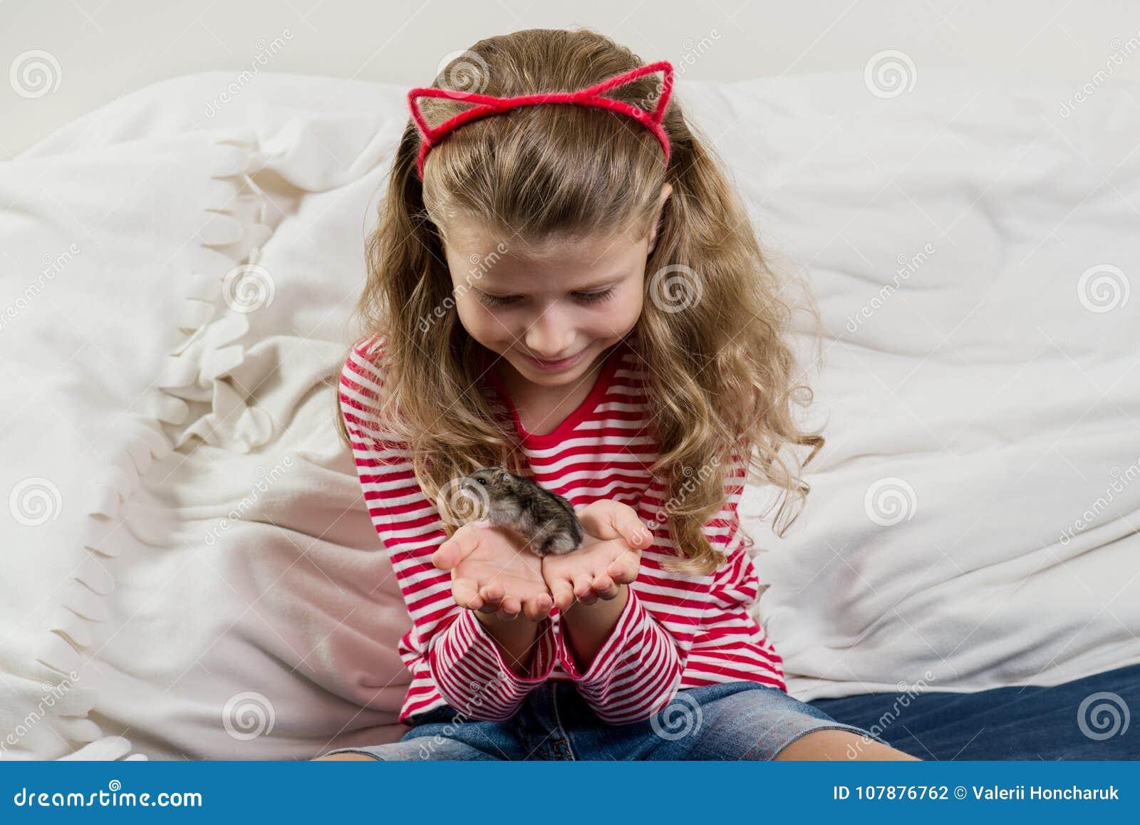 Petite fille adorable avec son animal familier - petit hamster