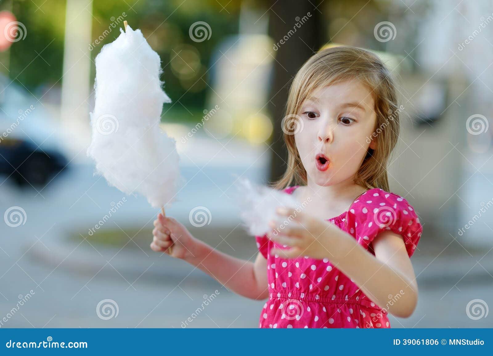Petite fille adorable mangeant la sucrerie-soie dehors