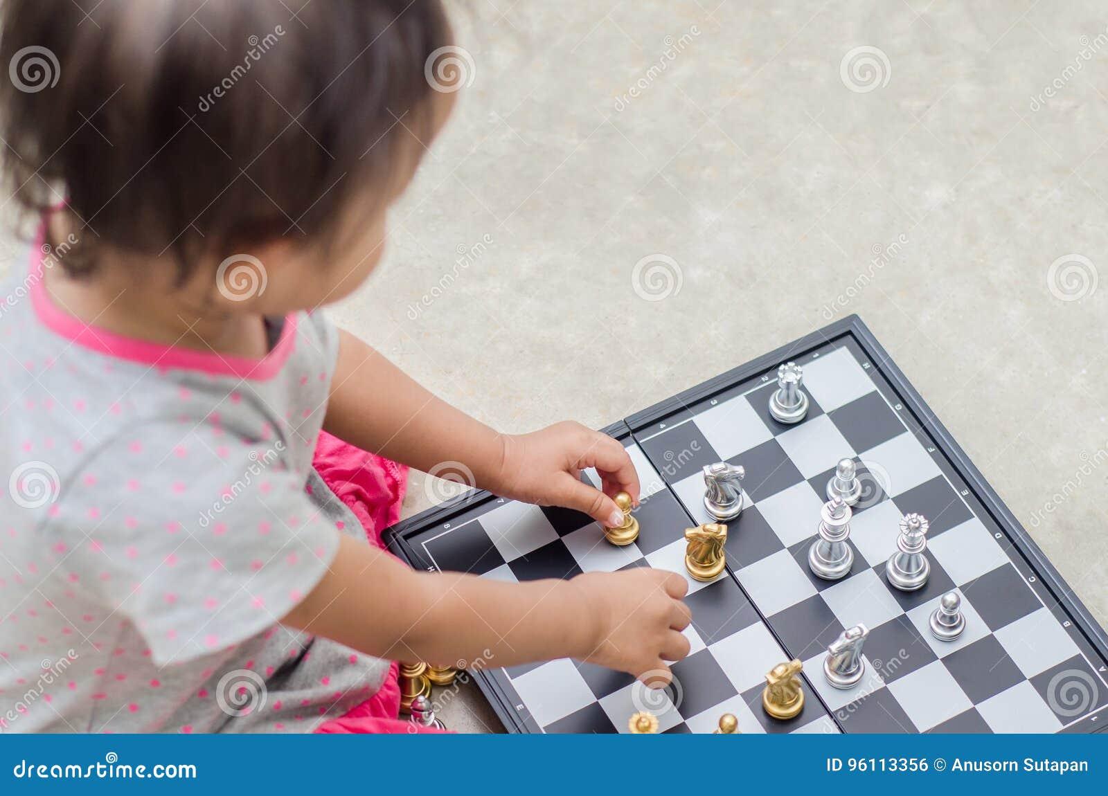 Petite fille asiatique avec le jeu d échecs à la maison