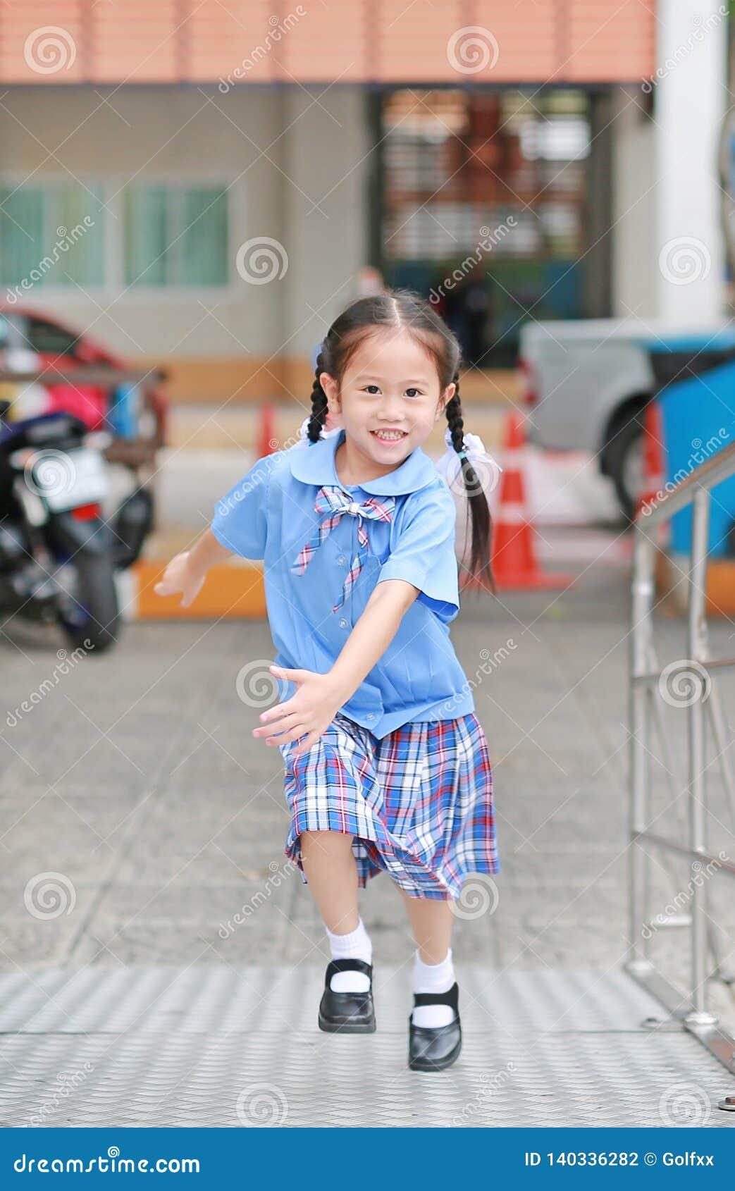 Petite fille asiatique de sourire d enfant dans l uniforme scolaire fonctionnant vers le haut de l escalier en métal
