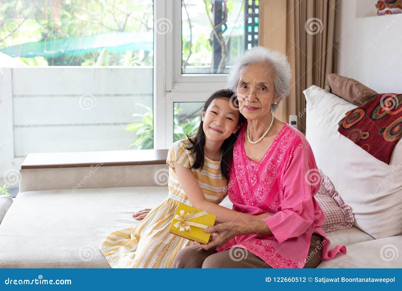 Petite fille asiatique et célébration supérieure de femme à la maison ensemble
