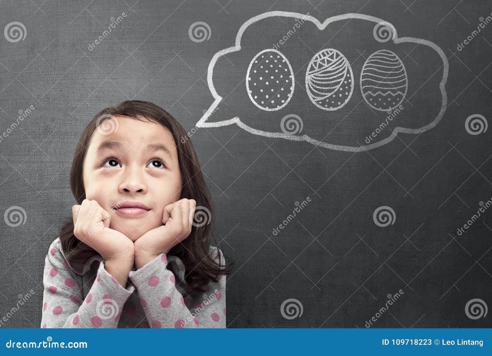 Petite fille asiatique heureuse rêvant de chasser des oeufs de pâques