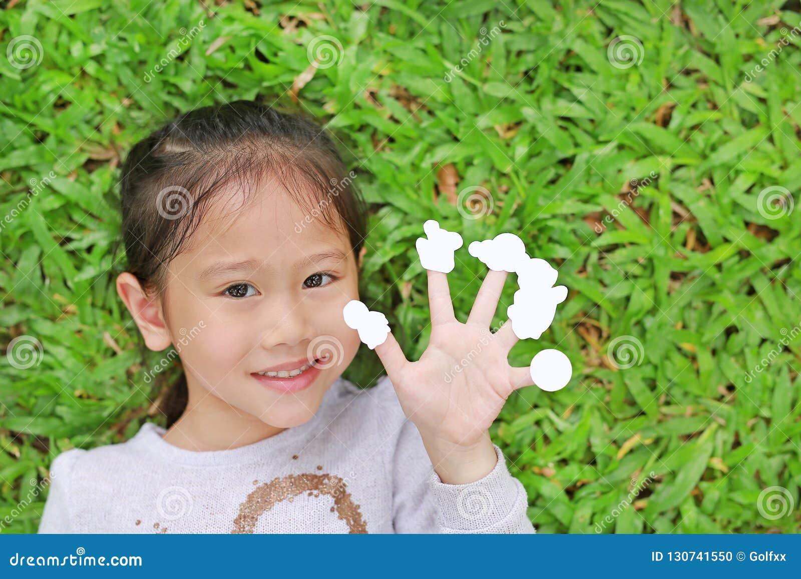 Petite fille asiatique mignonne d enfant se trouvant sur la pelouse d herbe verte avec les autocollants blancs vides d apparence