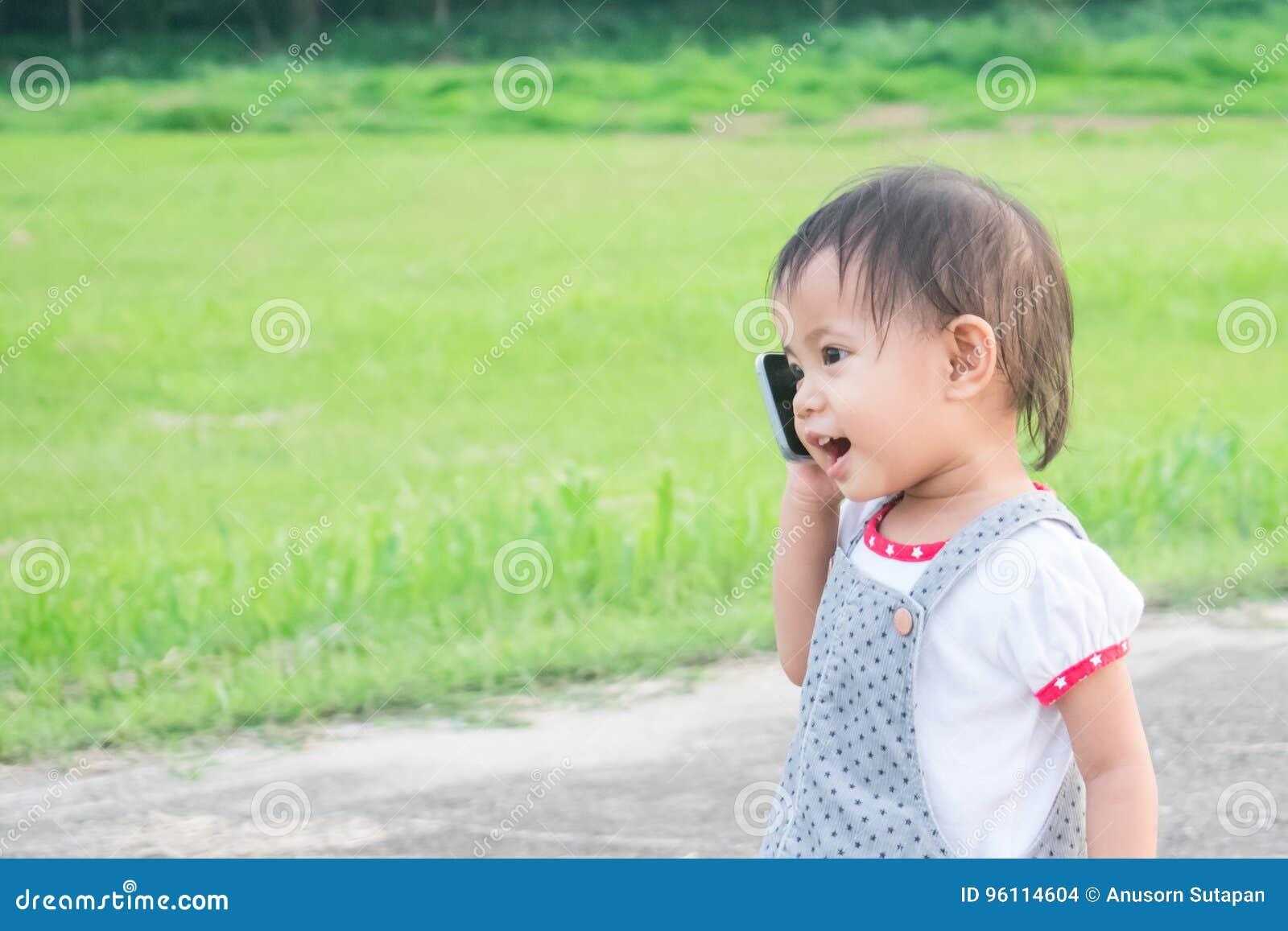 Petite fille asiatique parlant au téléphone intelligent en parc