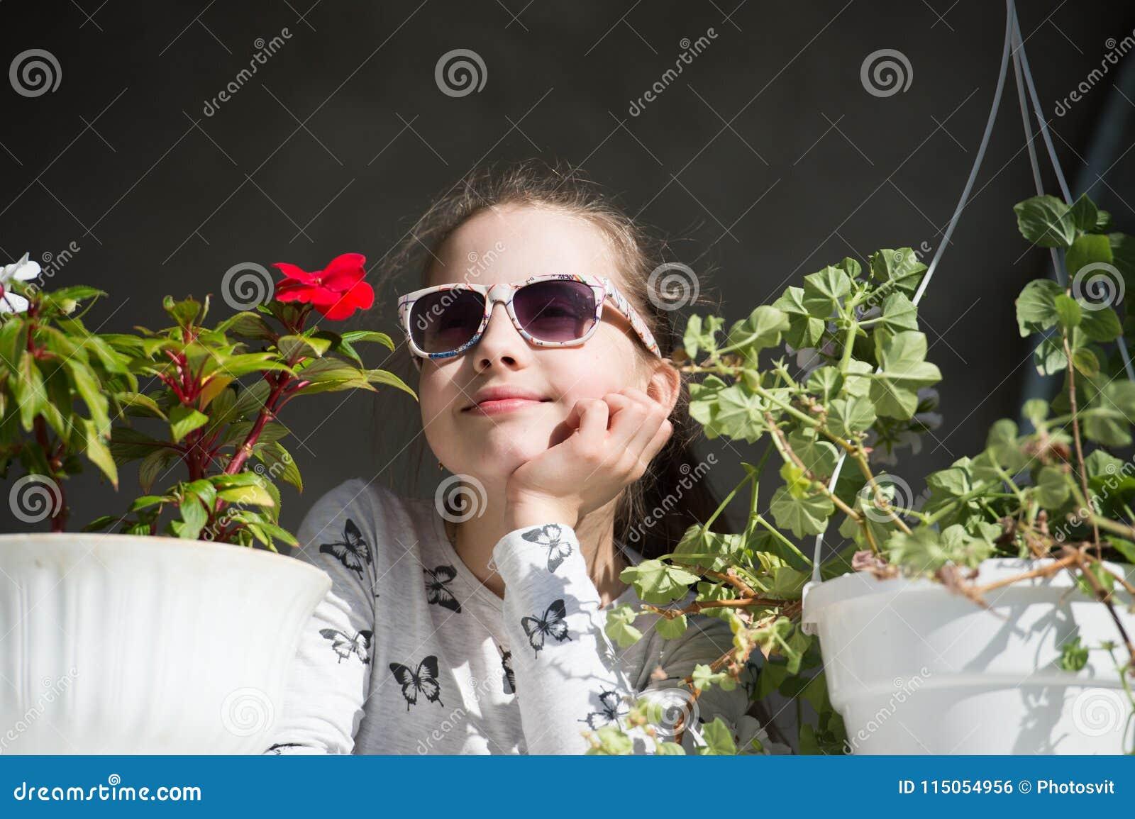 Petite fille avec des fleurs Lunettes de soleil d usage d enfant de mode le jour ensoleillé Enfant de beauté avec des pots d usin