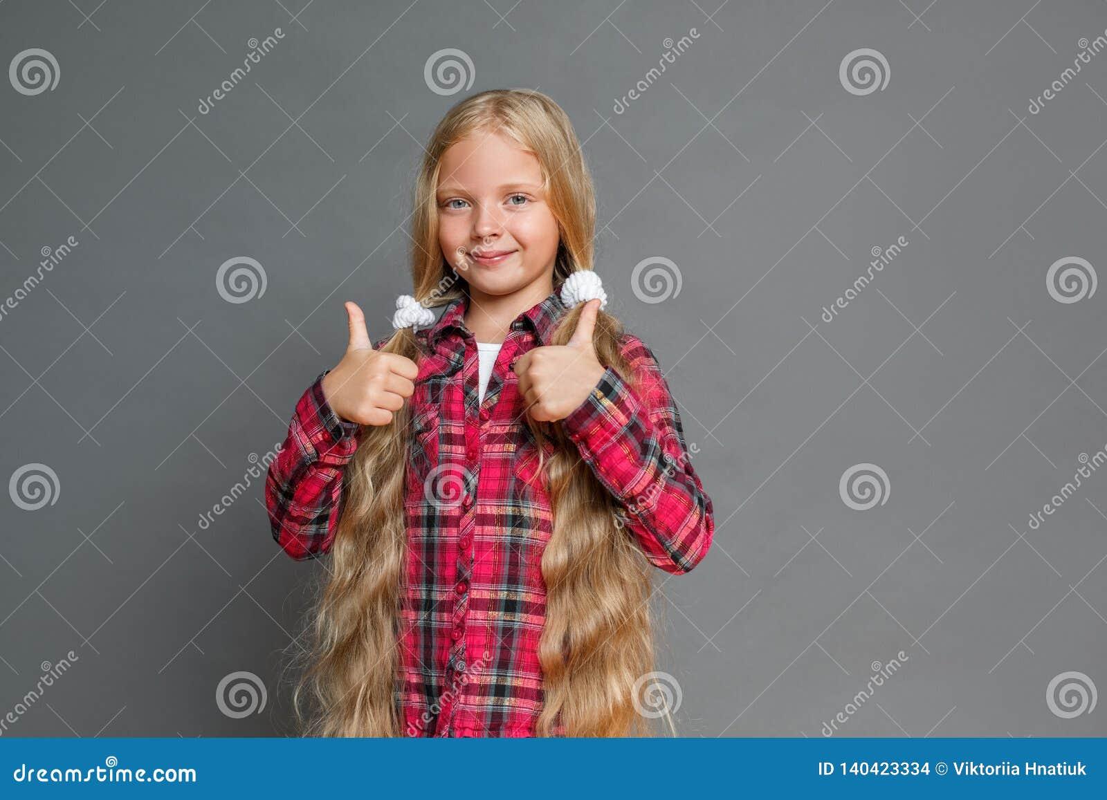 Petite fille avec des queues de cheval se tenant d isolement sur les pouces de représentation gris vers le haut de regarder la ca