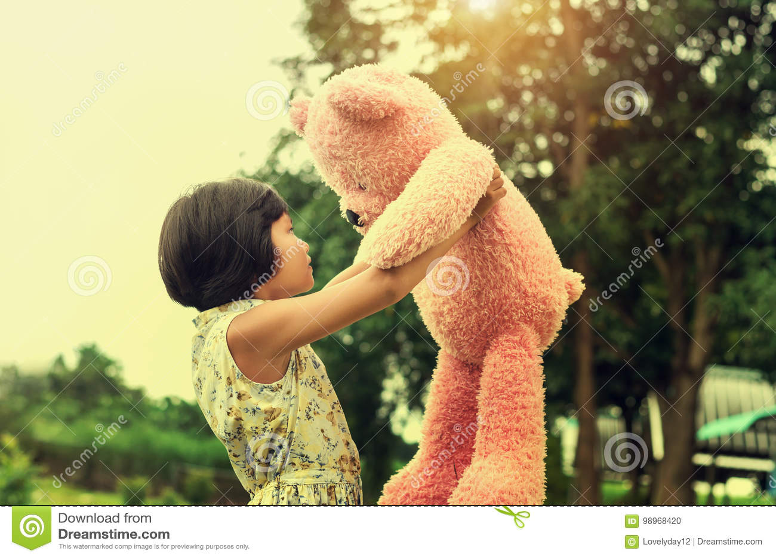 Petite fille avec la position et le coucher du soleil d ours de nounours