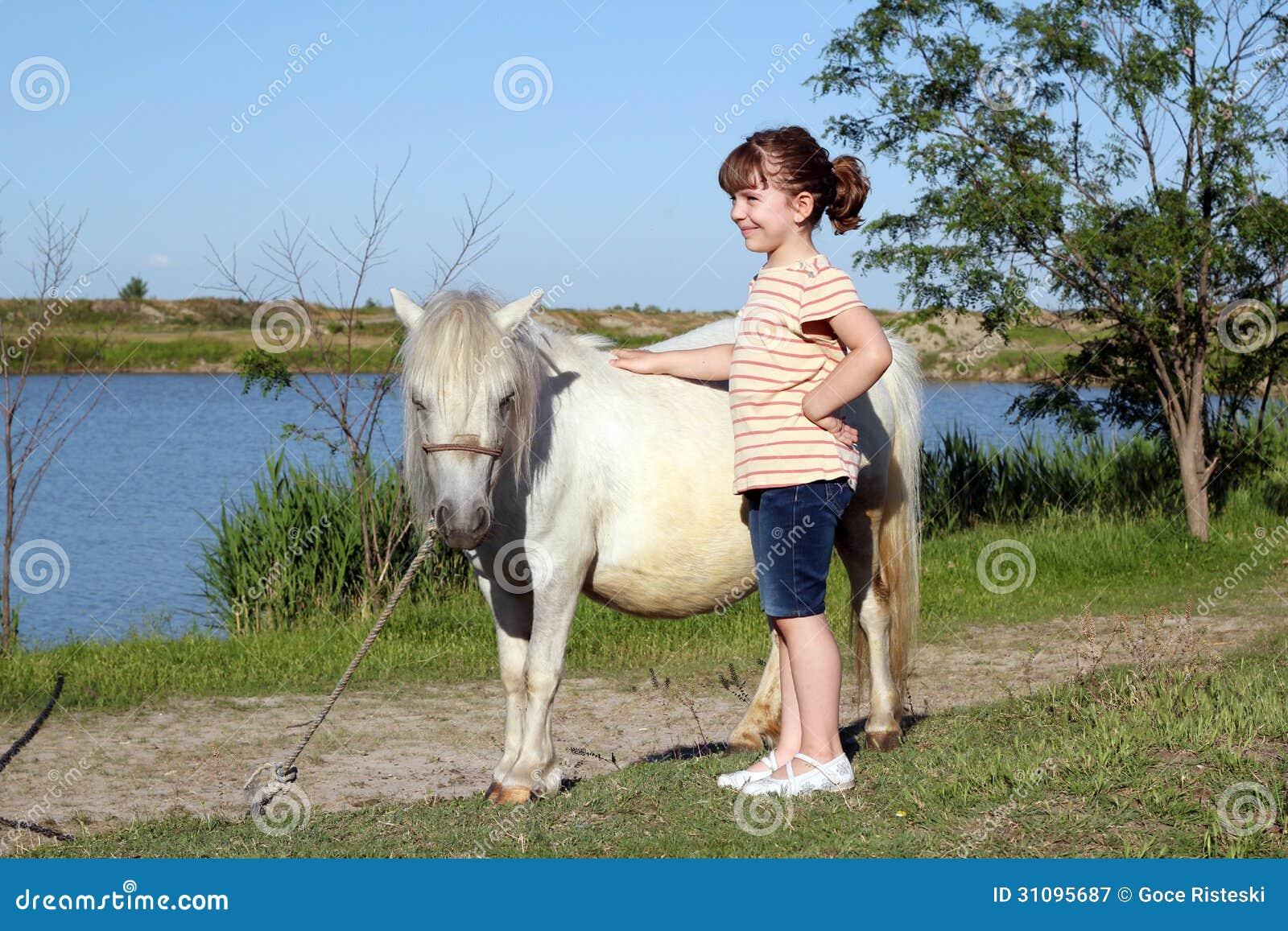 Petite fille avec le cheval de poney