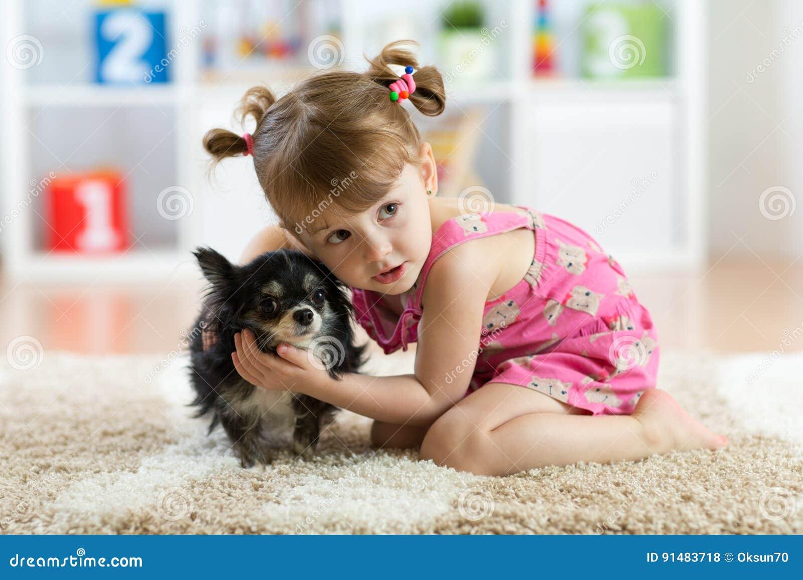 Petite fille avec le chien de chiwawa chez la pièce des enfants Amitié d animal familier d enfants