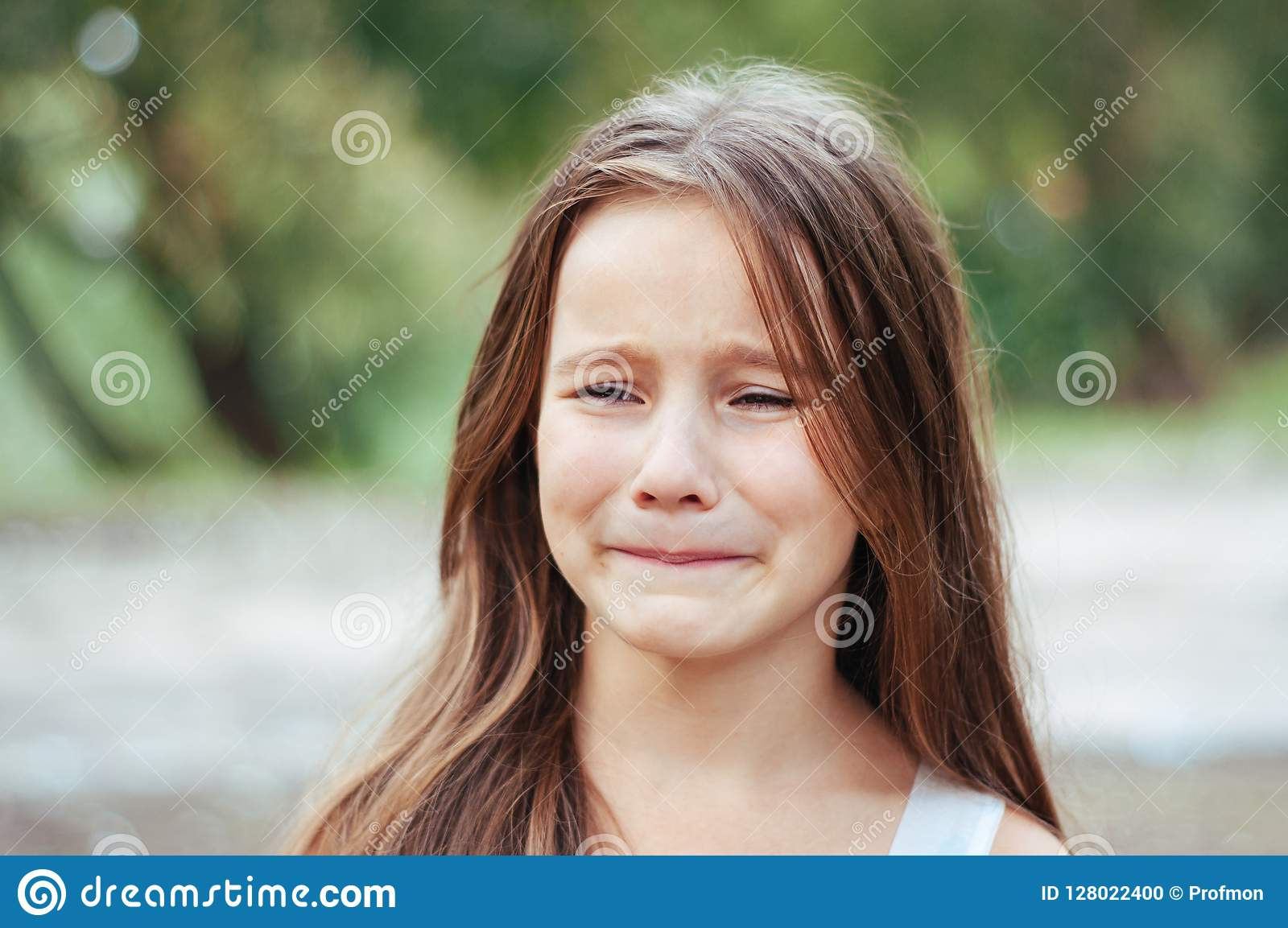 Petite fille avec le long portrait, pleurer avec émotion et le renversement de cheveux, éclairage naturel dehors