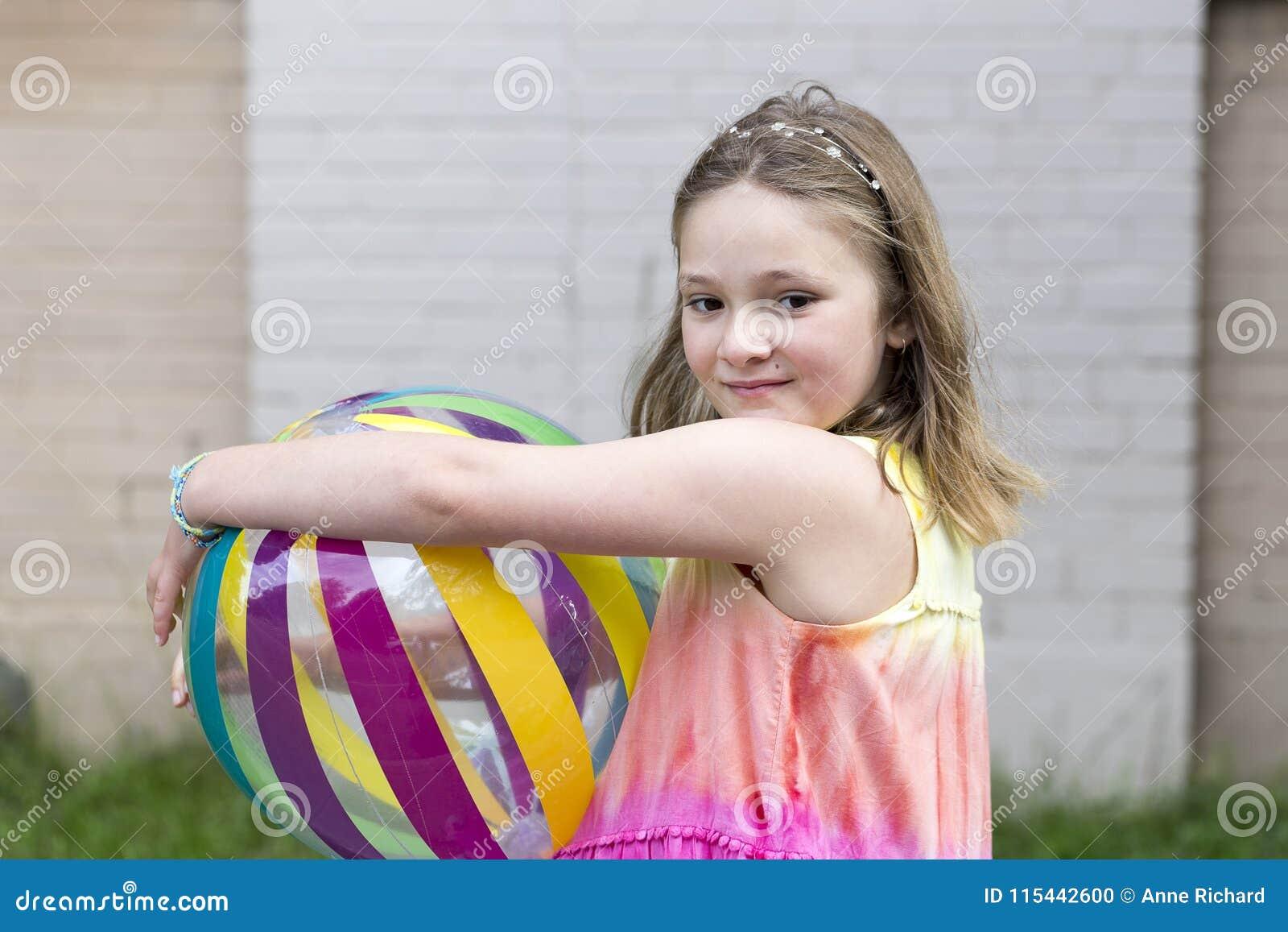 Petite fille avec le sembler rêveur tenant le ballon de plage multicolore