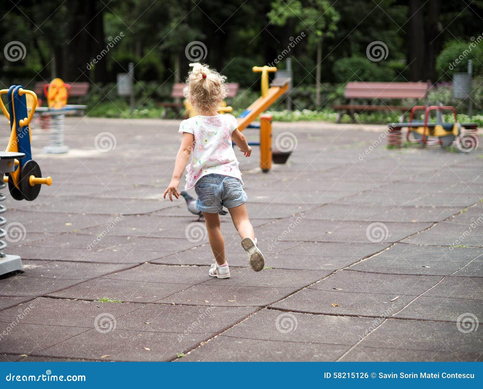Petite fille blonde courant dans le terrain de jeu