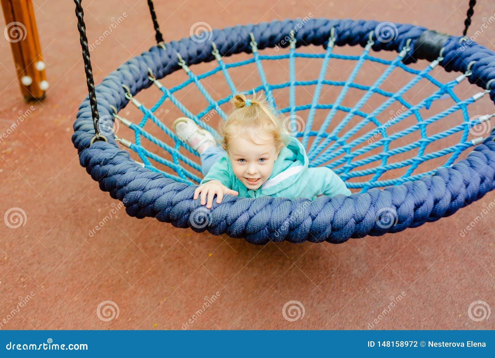 Petite fille blonde heureuse ayant l amusement sur un terrain de jeu