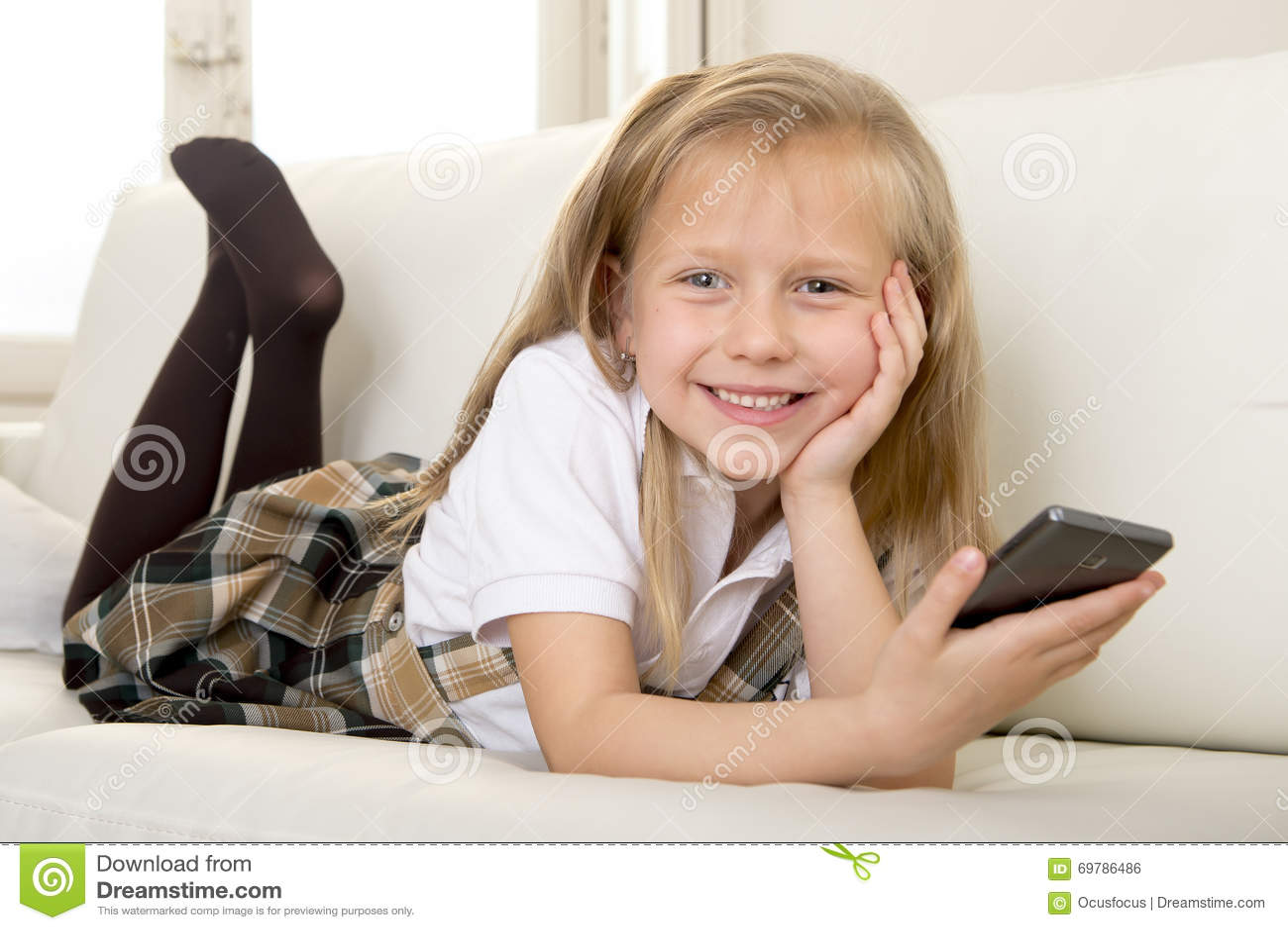 petite fille blonde heureuse sur le sofa la maison utilisant l 39 internet app au t l phone. Black Bedroom Furniture Sets. Home Design Ideas