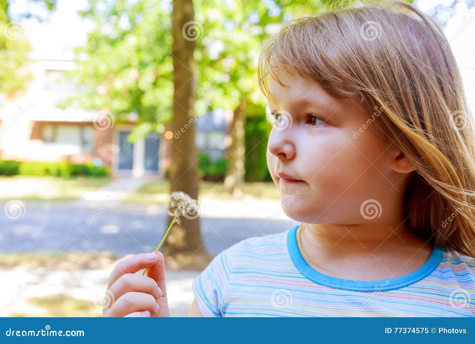Petite fille blonde mignonne soufflant un pissenlit
