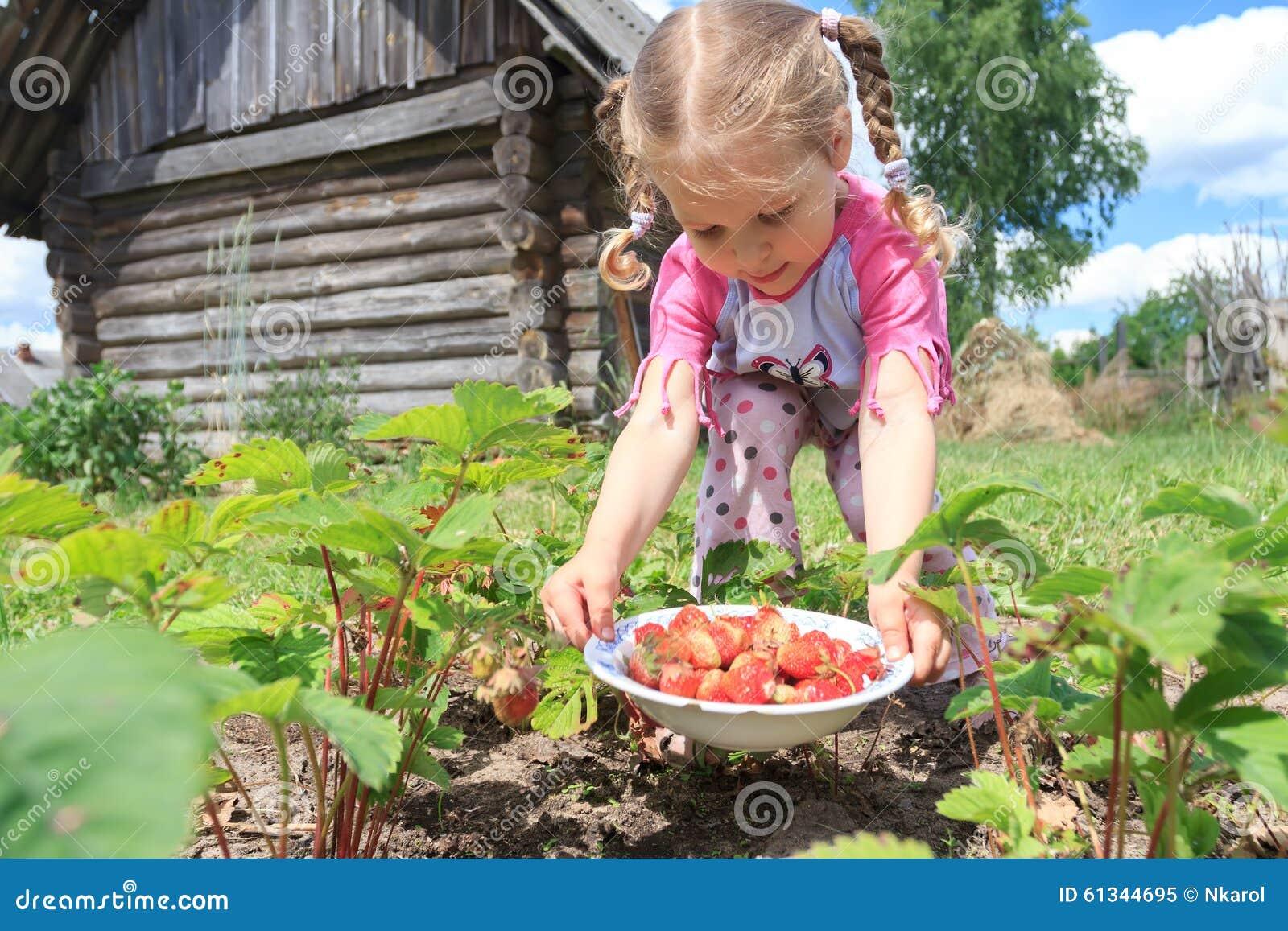 Petite fille blonde moissonnant le jardin du pays