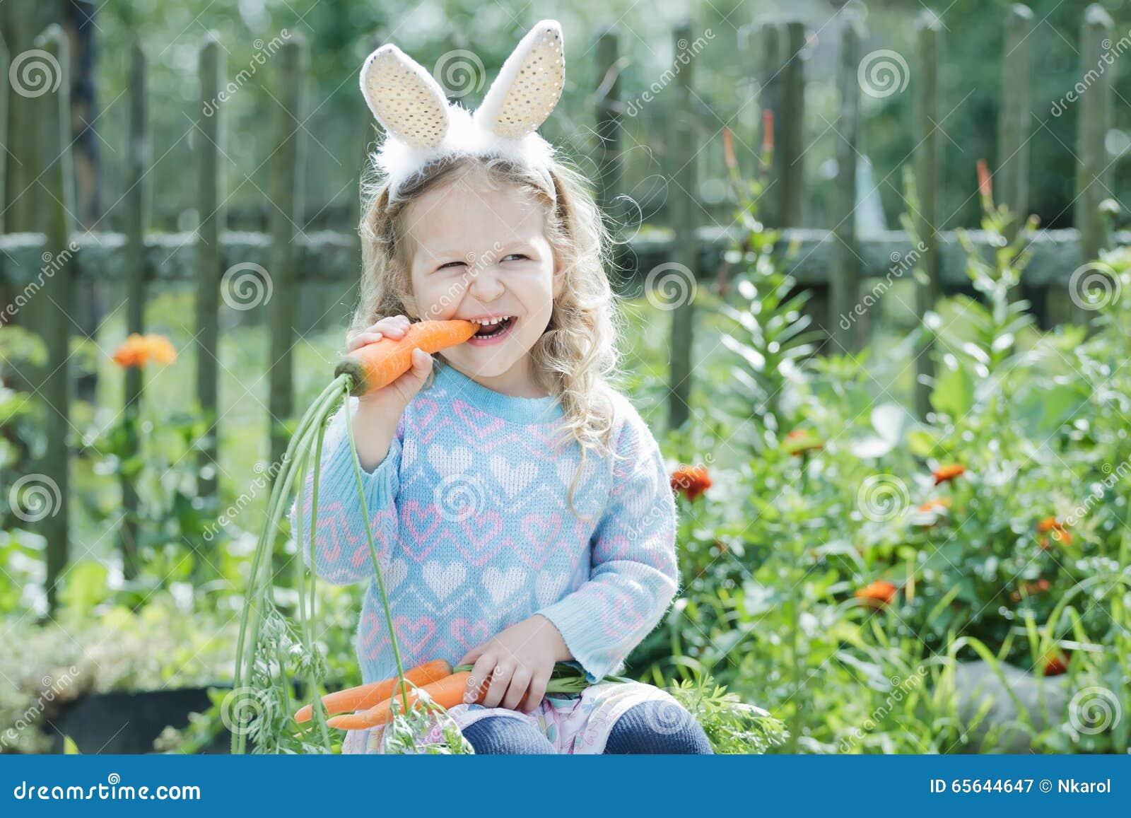 Petite fille blonde utilisant les oreilles drôles de lapin de DIY rongeant la carotte fraîche