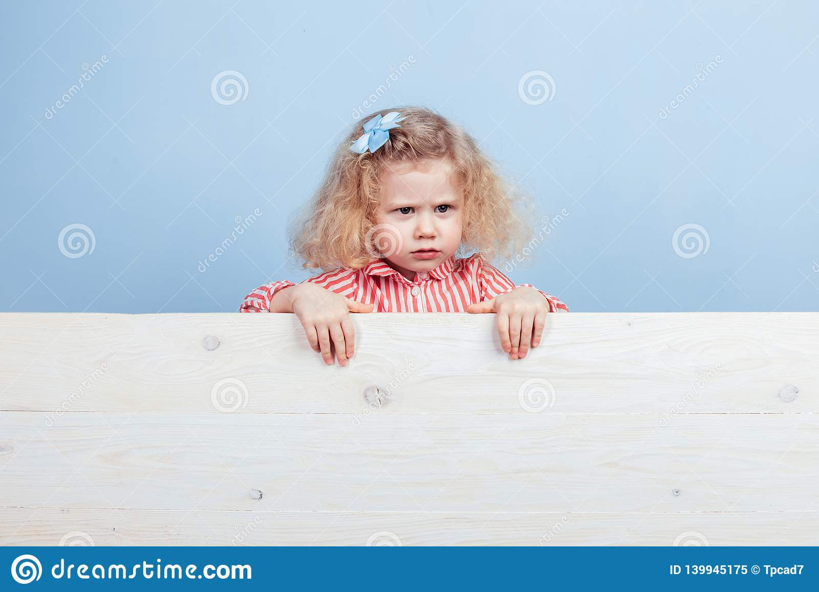 Petite fille bouclée drôle dans une robe rouge et blanche rayée et une fleur bleue sur ses supports de cheveux derrière le consei
