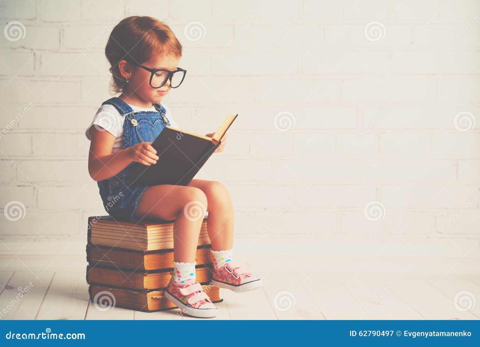 Petite fille d enfant avec la lecture en verre livres