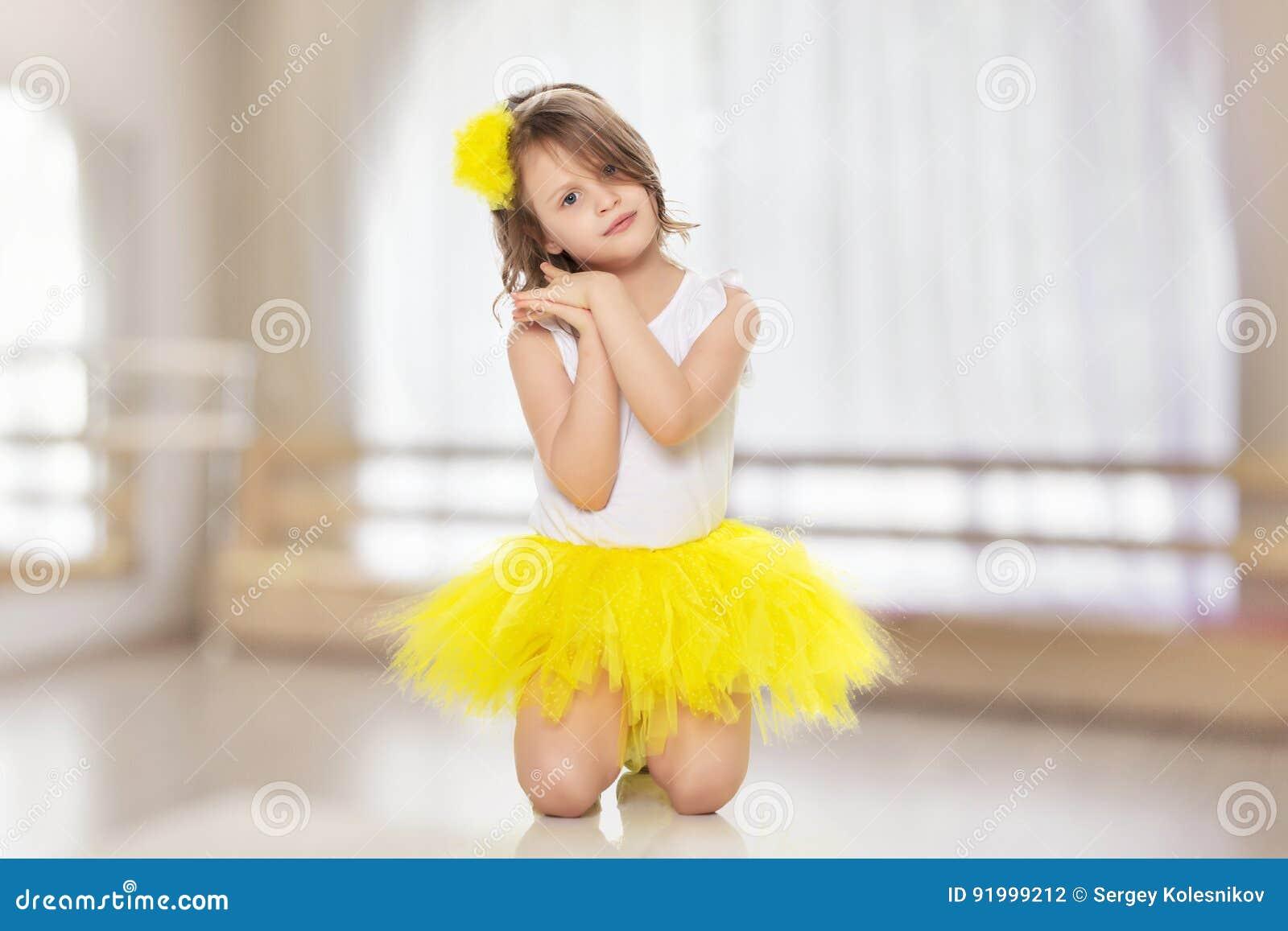 18f3063b7021a Fille blonde assez petite dans une jupe jaune lumineuse courte et un  chemisier blanc Elle se met à genoux et doucement regardant  l appareil-photo avec les ...