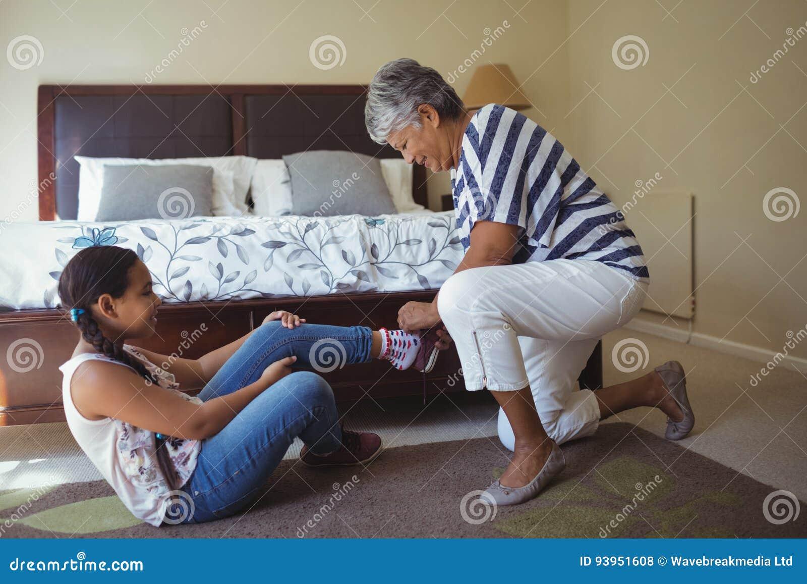 Petite Fille De Aide De Grand Mère Pour Porter Des Chaussures Dans La Chambre  De Lit à La Maison