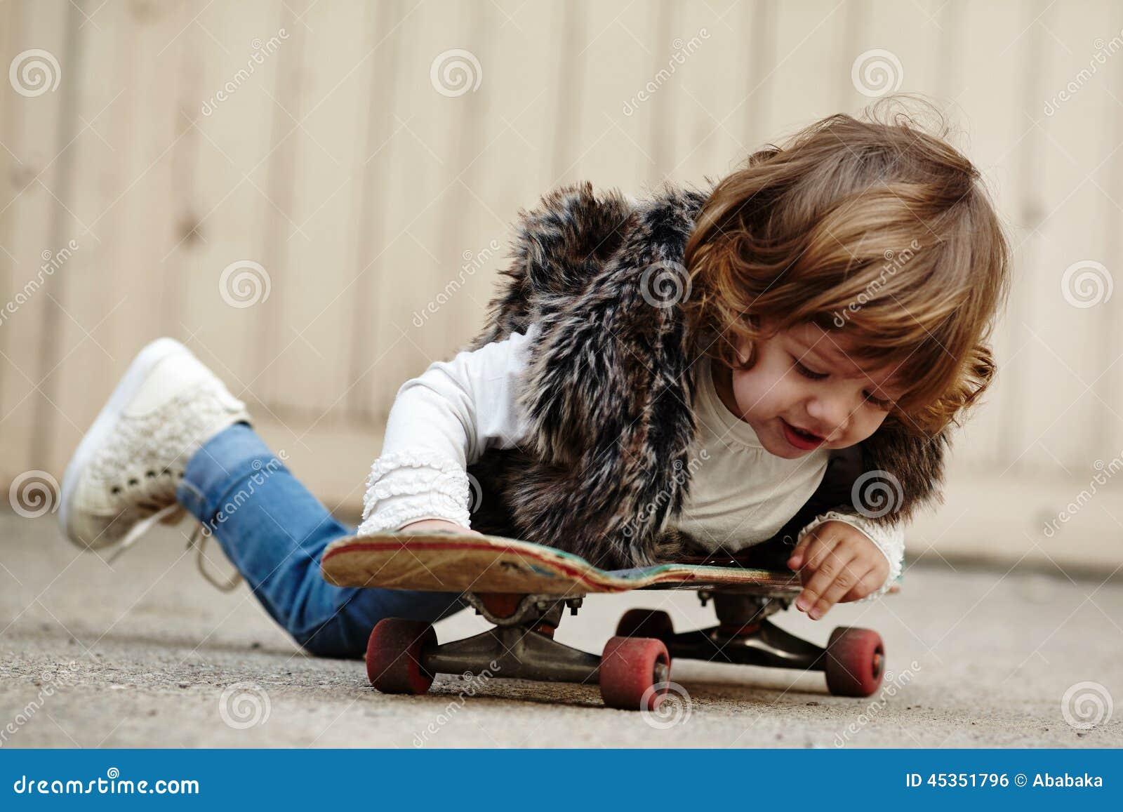 Petite fille de hippie avec le portrait de planche à roulettes