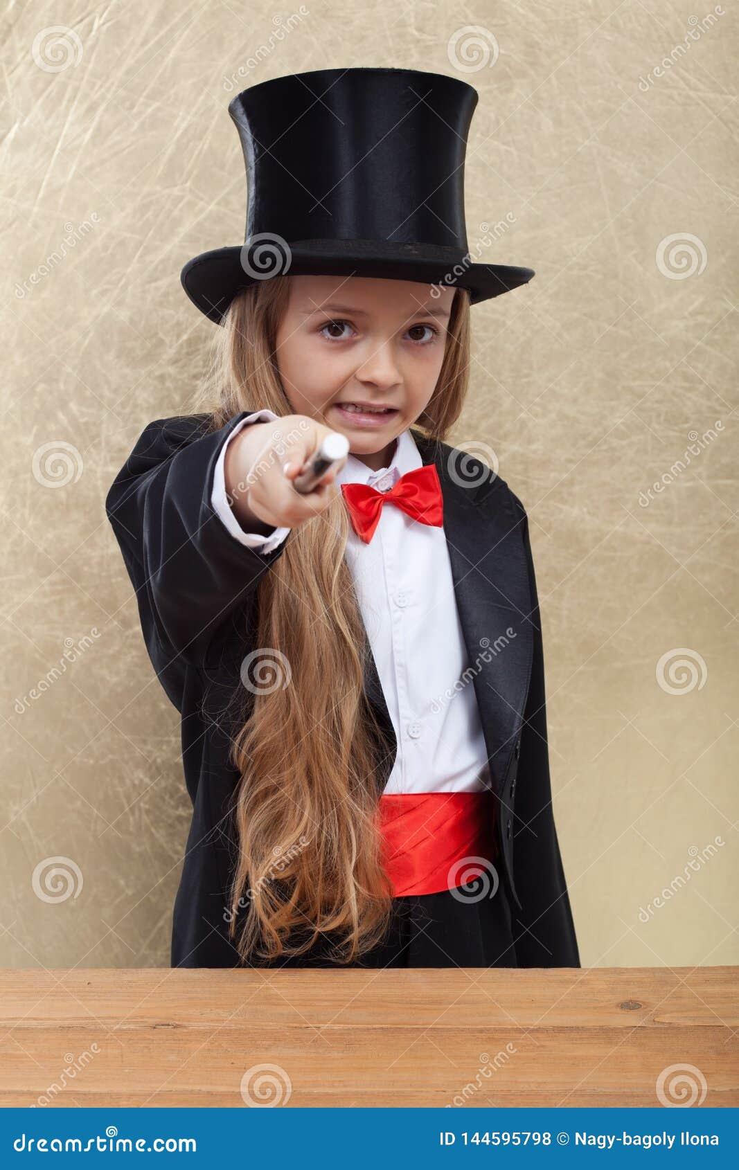Petite fille de magicien exécutant tour de magie mauvais - indiquant avec la baguette magique la visionneuse
