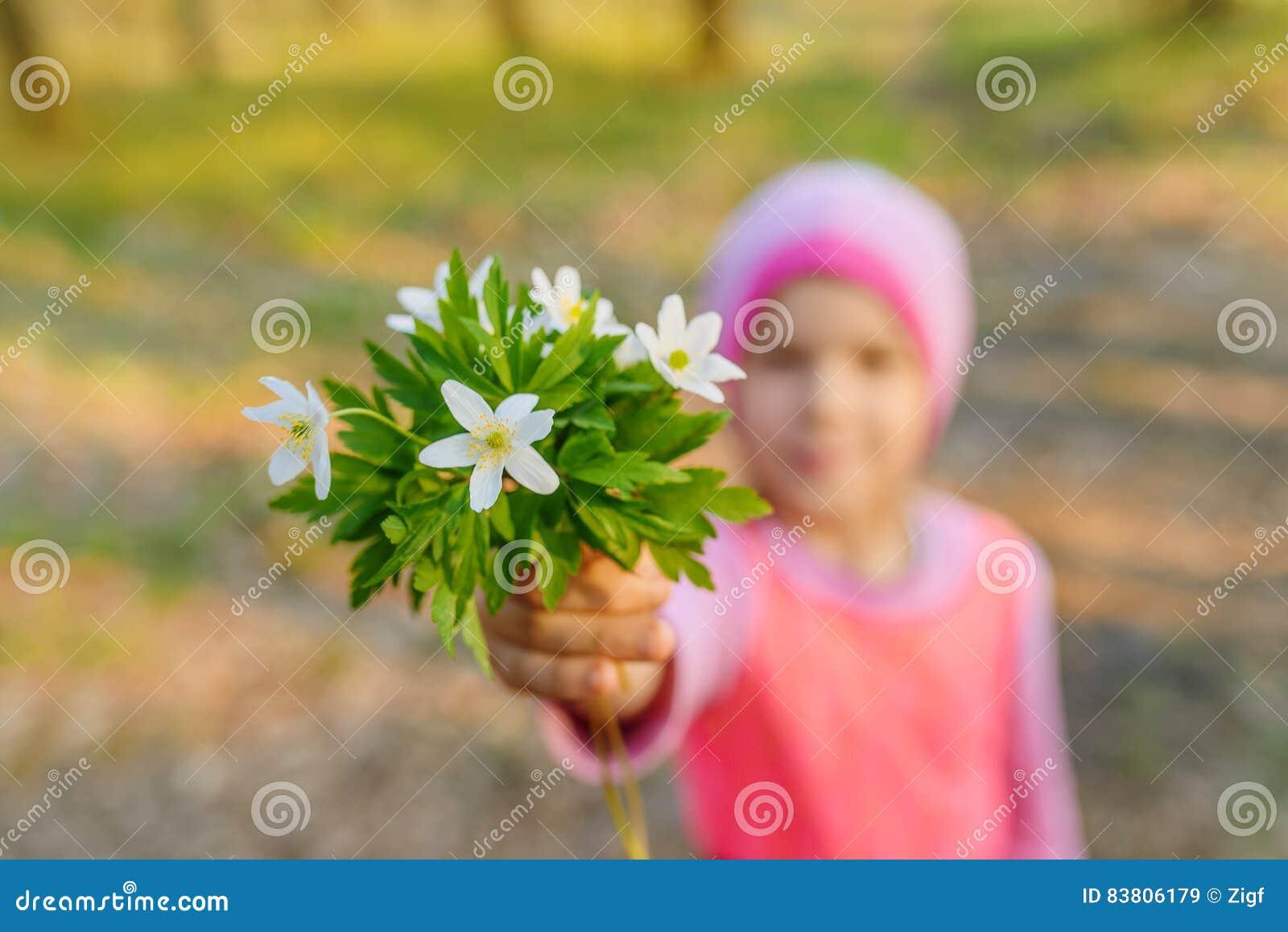 Petite fille de sourire avec le nemorosa d anémone