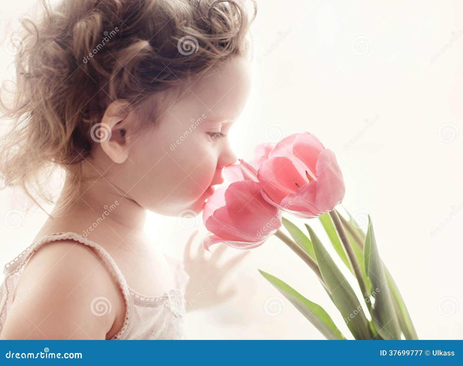 Petite fille douce avec les tulipes roses contre la lumière du soleil de matin.