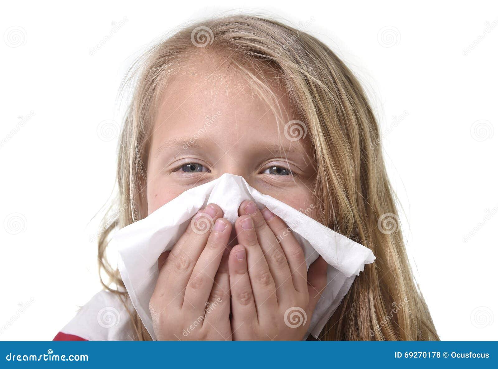 Petite fille douce et mignonne de cheveux blonds soufflant son nez avec le tissu de papier ayant un malade froid de sentiment