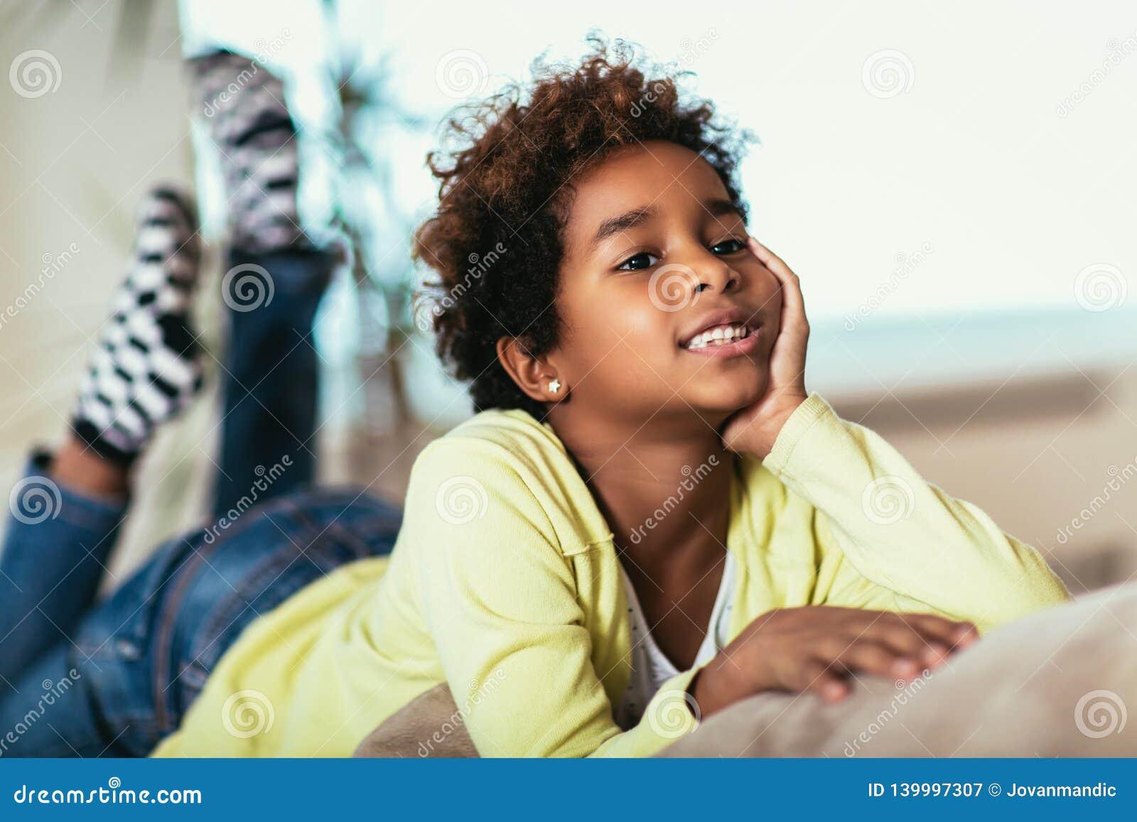 Petite fille drôle d afro-américain regardant la caméra, enfant de sourire de métis posant pour le portrait à la maison