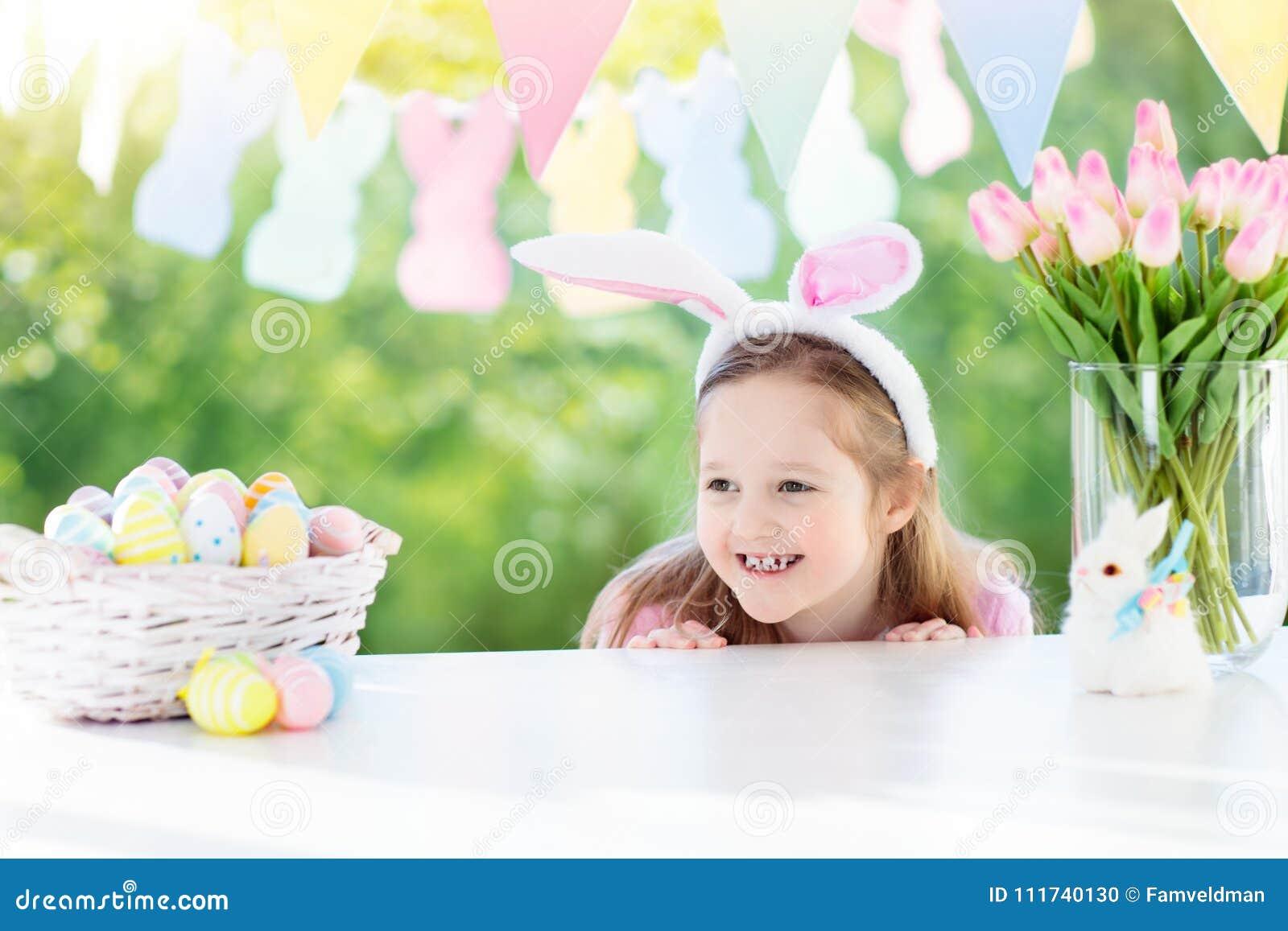 Petite Fille Drole Dans Des Oreilles De Lapin Au Petit Dejeuner Le Matin De Paques A La Table Avec Des Oeufs De Paques Photo Stock Image Du Fille Petite 111740130